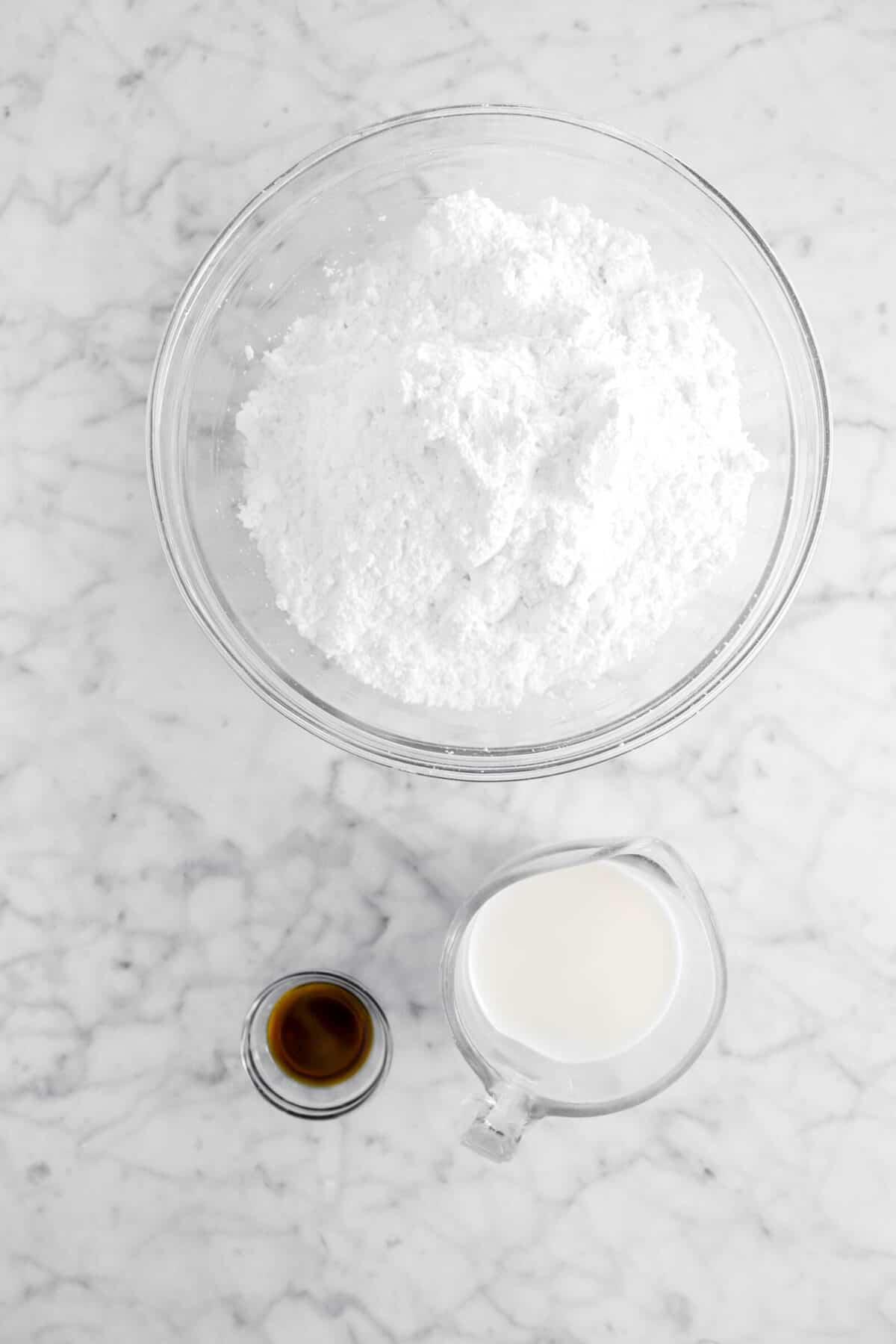 powdered sugar, milk, and vanilla on marble counter