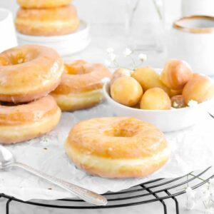 glazed doughnuts on wire cooling rack with doughnut holes in a white bowl, flowers, a stack of doughnuts behind