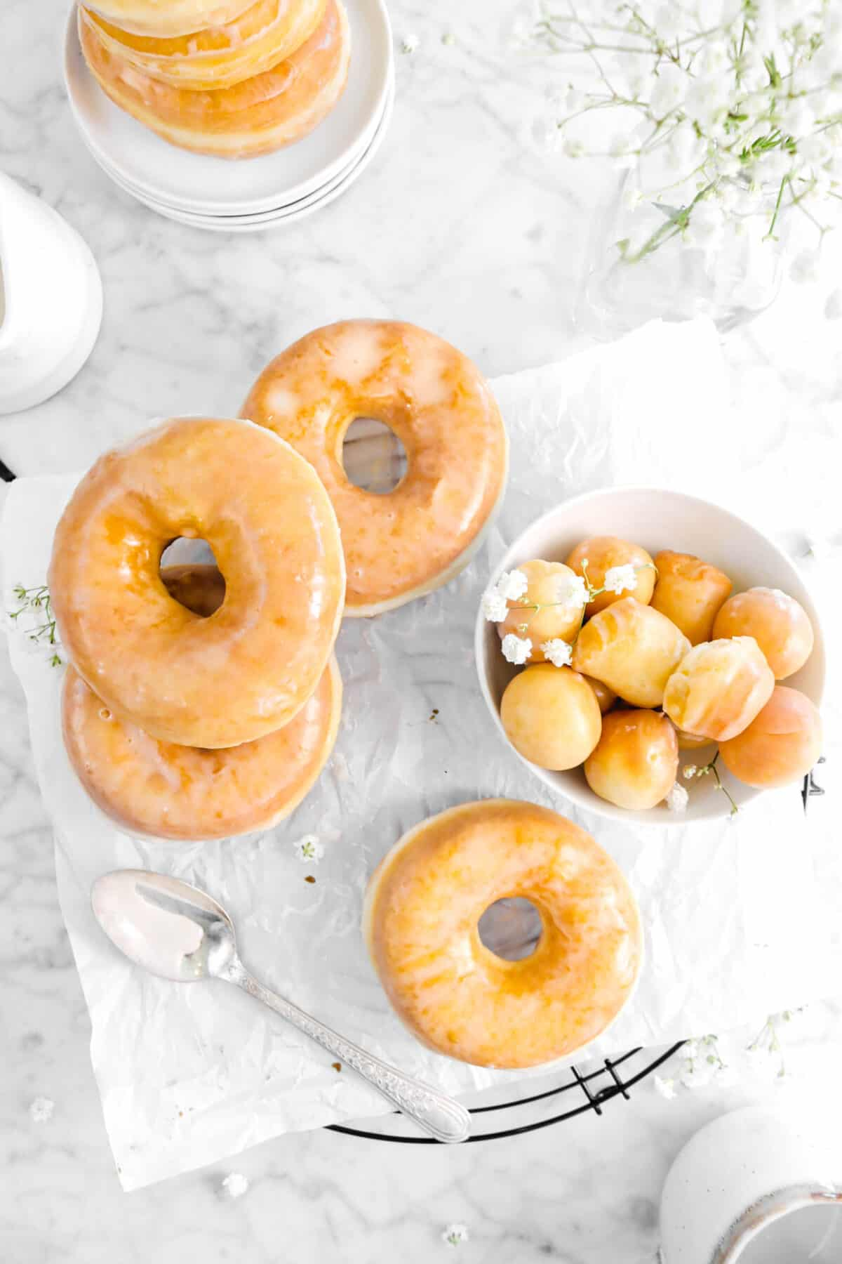 overhead shot of four doughnuts on wire cooling rack with doughnut holes, a spoon, and flowers