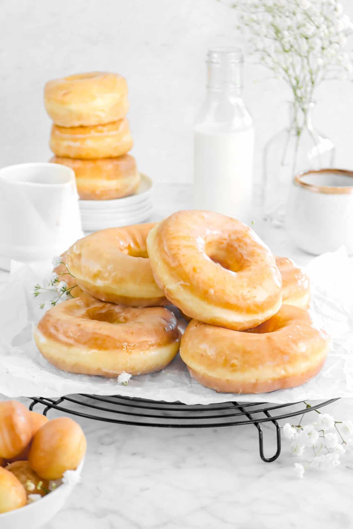 doughnuts stacked on a wire cooling rack with flowers, stacked doughnuts behind, a glass of milk, and coffee mug