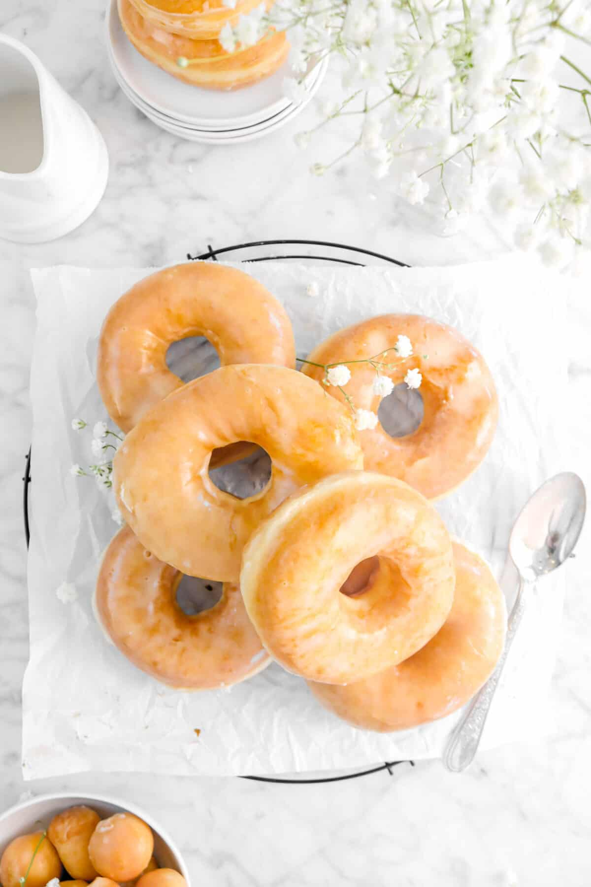 overhead shot of doughnuts on parchment paper with flowers and a spoon
