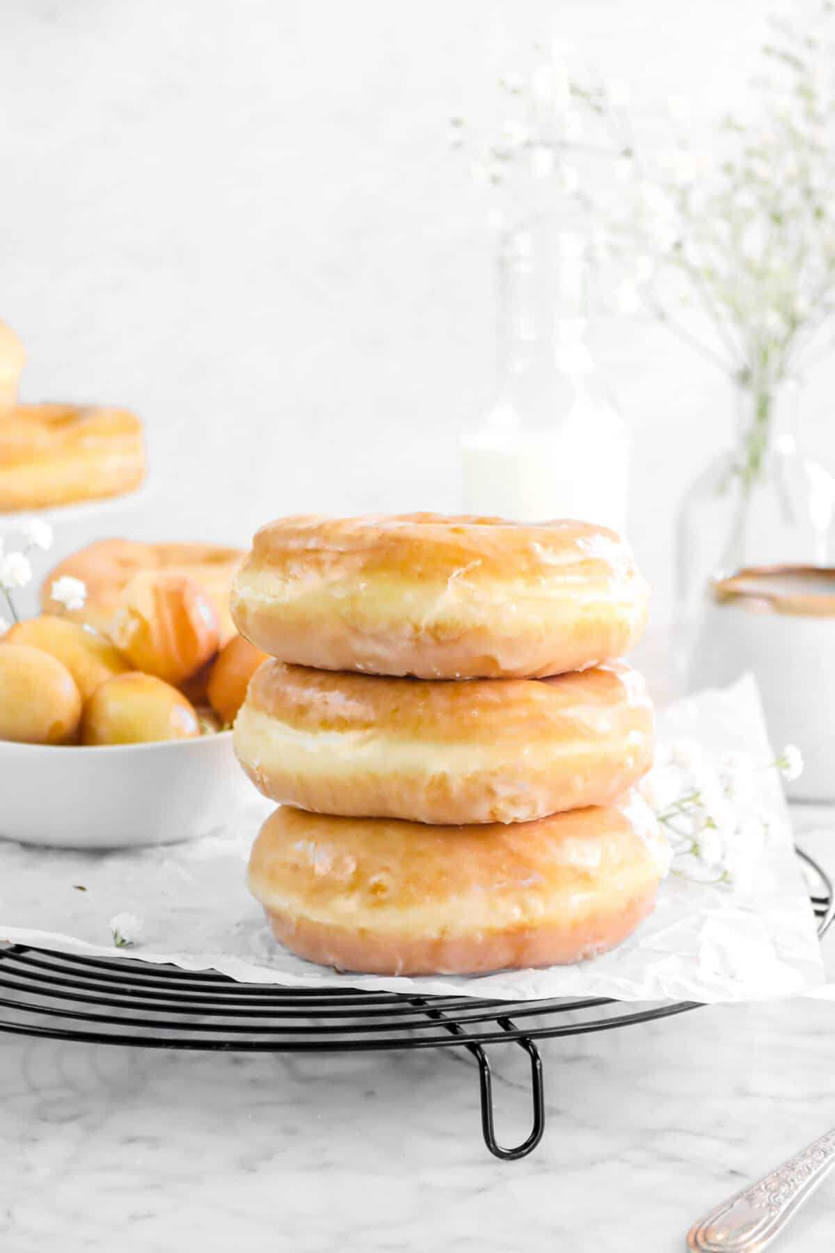 three stacked doughnuts on wire cooling rack with more doughnuts behind, flowers, and glass of milk