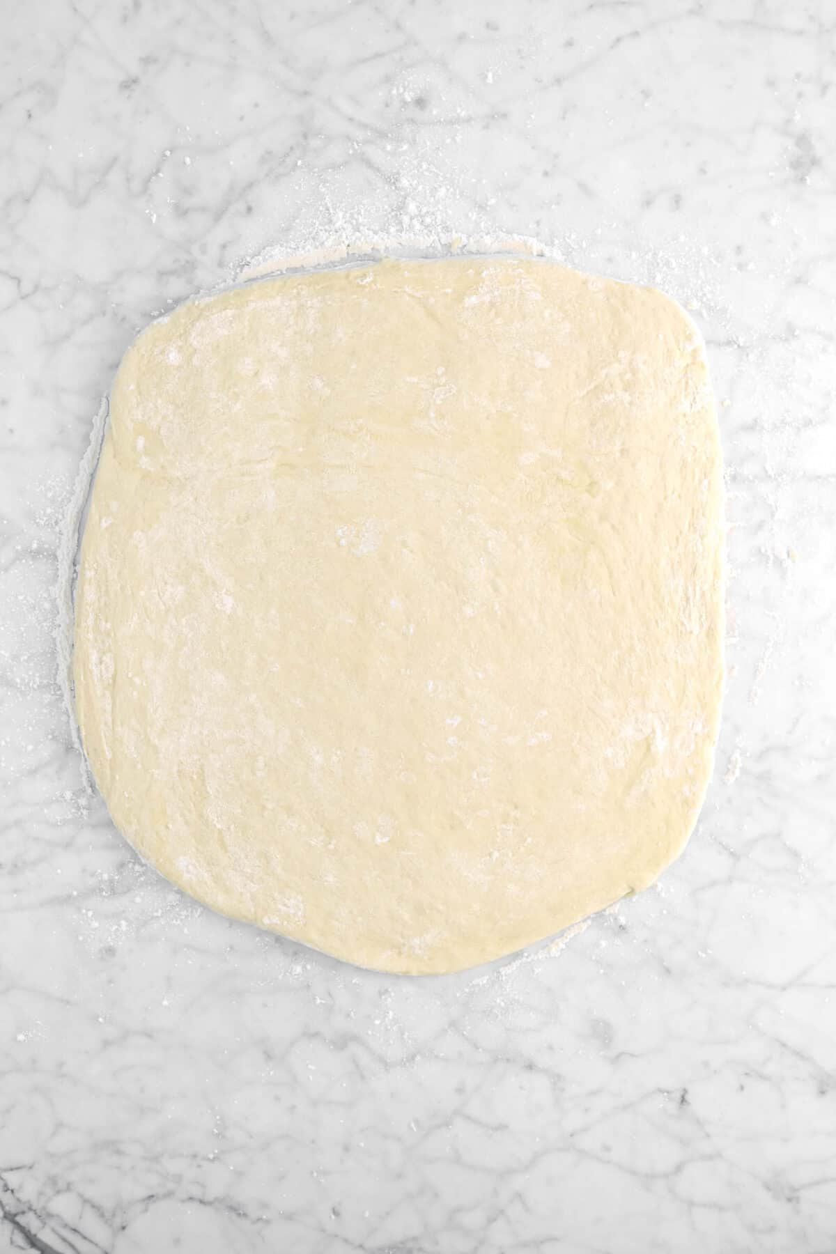 dough rolled out on marble counter