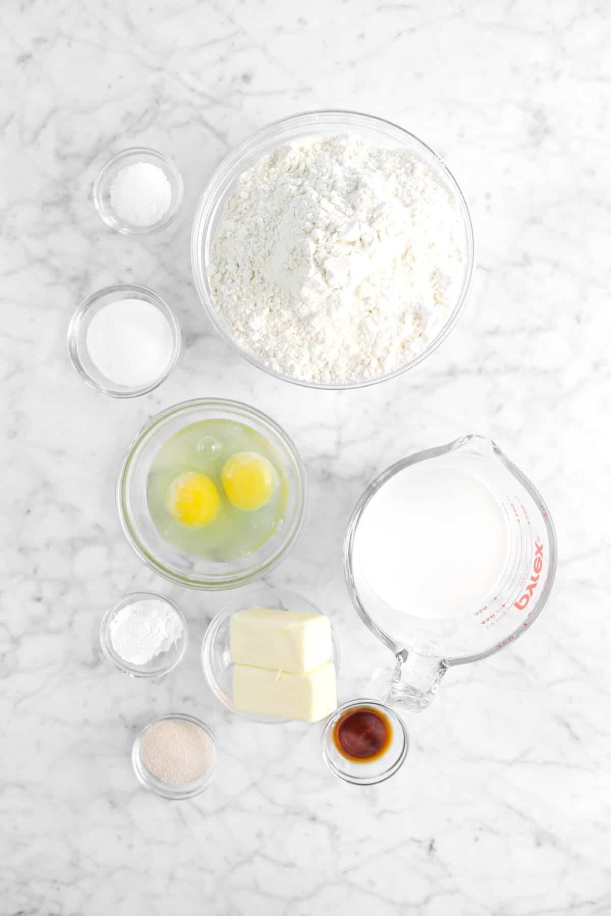 salt, sugar, flour, eggs, milk, butter, baking powder, yeast, and vanilla on marble counter