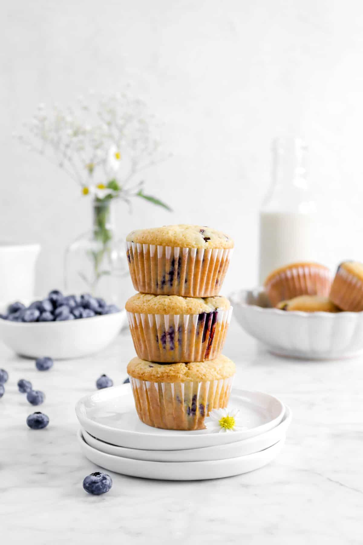 three stacked muffins on three stacked plates with flowers, blueberries, a glass of milk, and more blueberry muffins behind