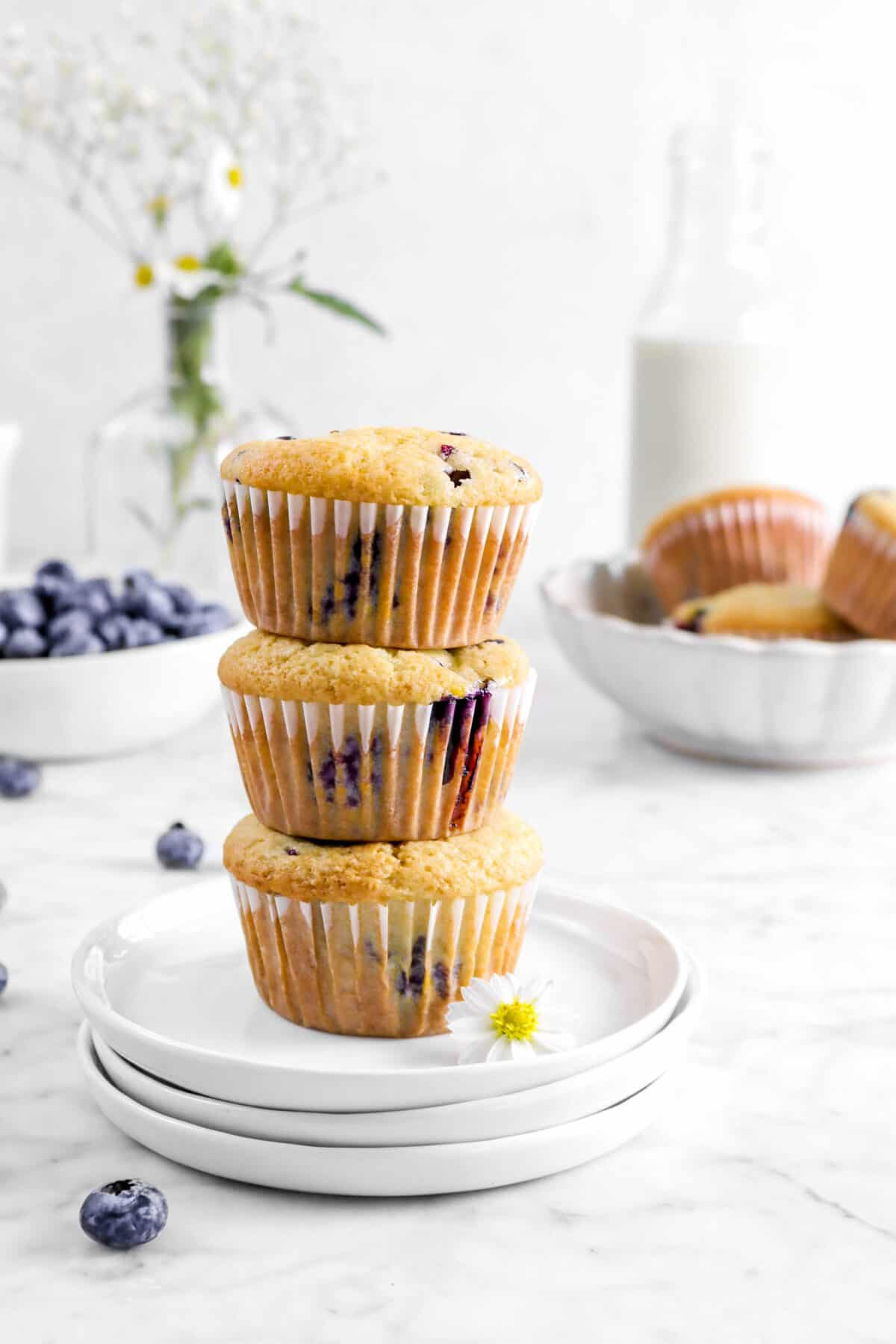 close up of three stacked blueberry muffins on white paltes with blueberries, flowers, and more muffins behind