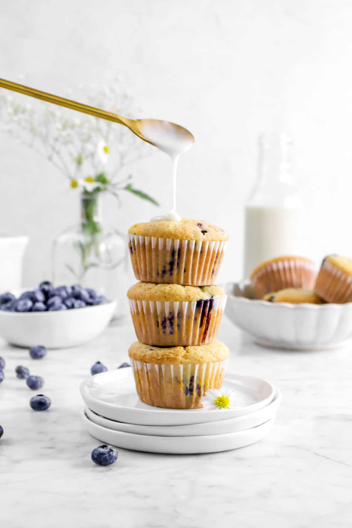 glaze being drizzled onto three stacked blueberry muffins with flowers, fresh blueberries, more muffins, and glass of milk behind