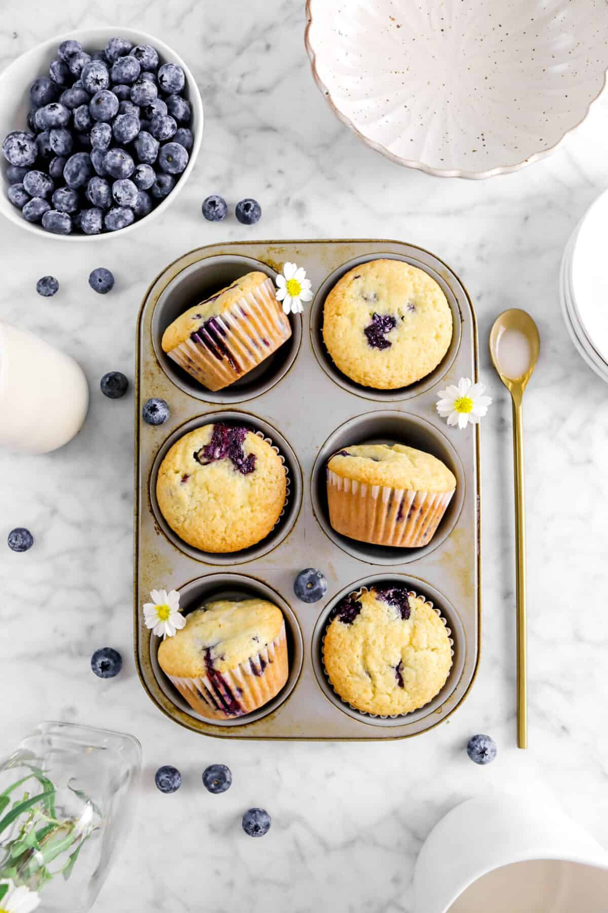 overhead shot of blueberry muffins in small cupcake pan with gold spoon, blueberries, flowers, and bowls around
