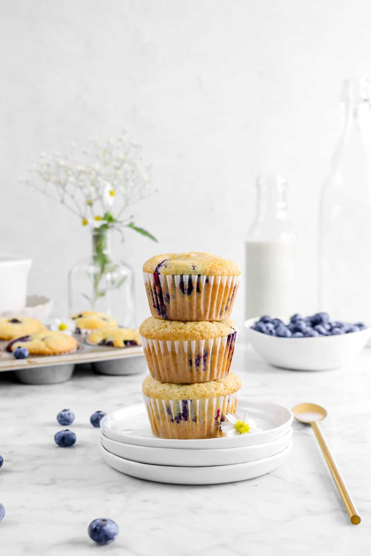 three stacked blueberries with pan of blueberry muffins behind, fresh blueberries, flowers, and gold spoon