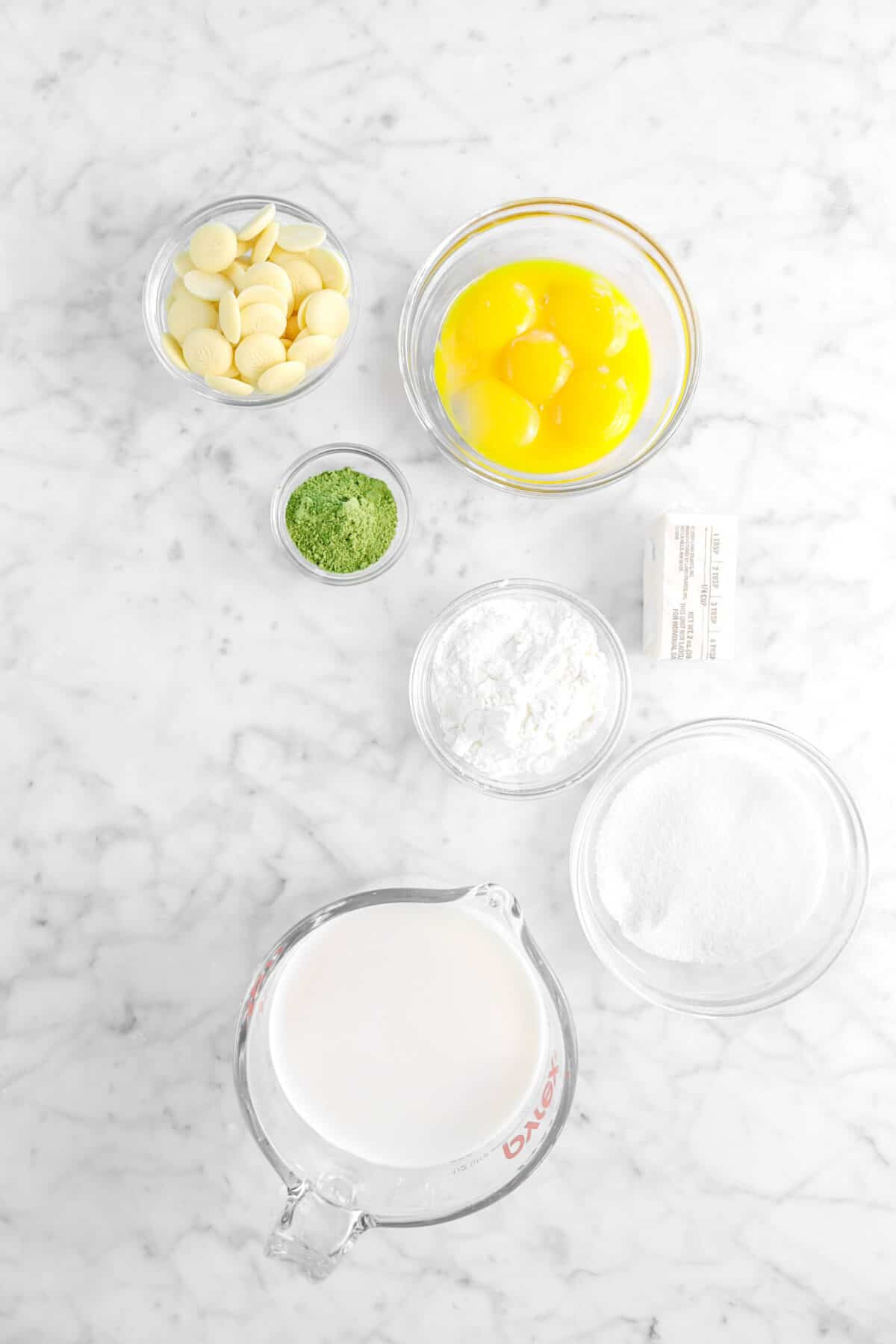 white chocolate, egg yolks, matcha, butter, corn starch, sugar, and milk on marble counter