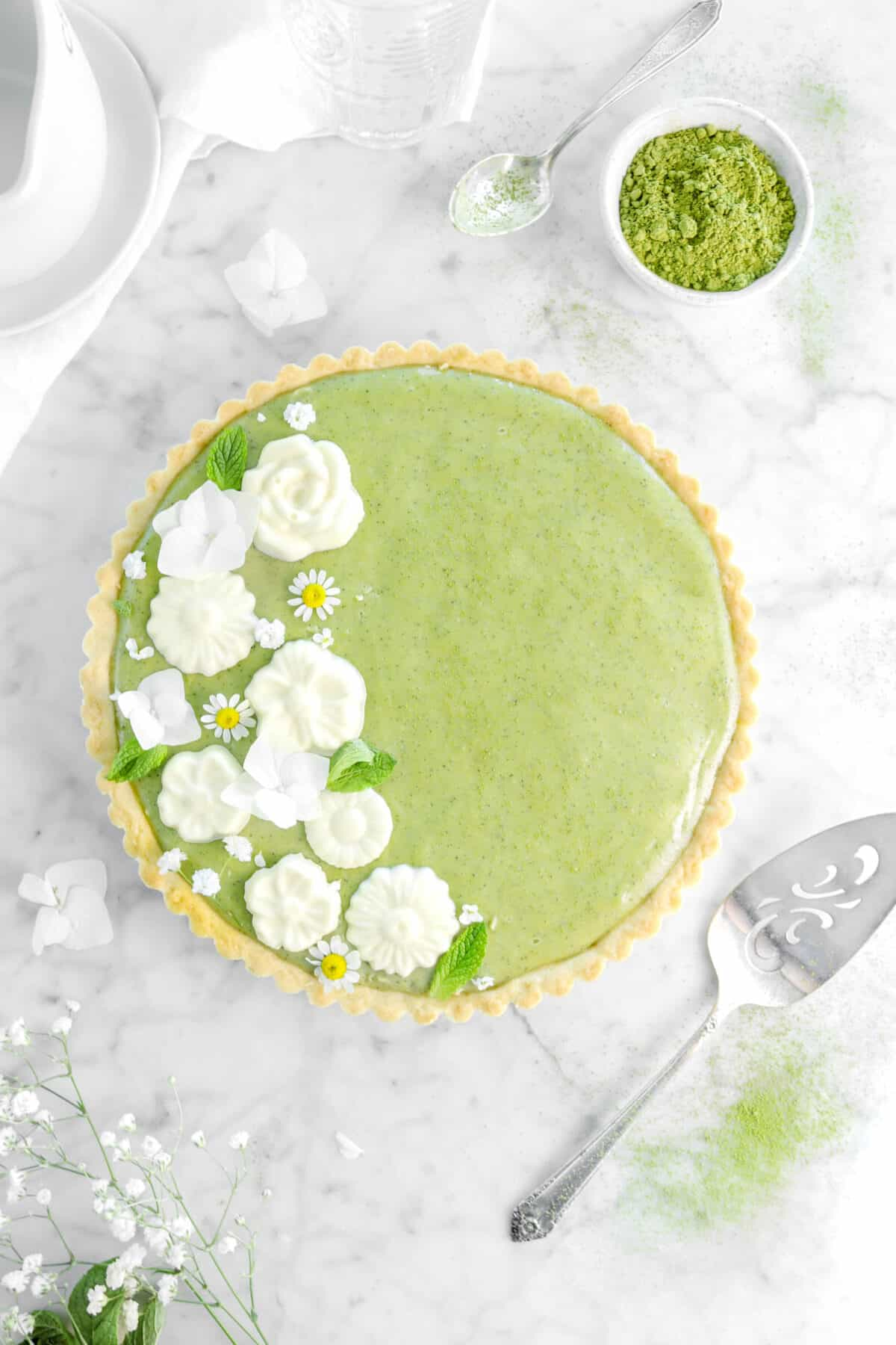 matcha tart on marble counter with white chocolate flowers, mint leaves, other flowers, cake knife, matcha powder, and a napkin