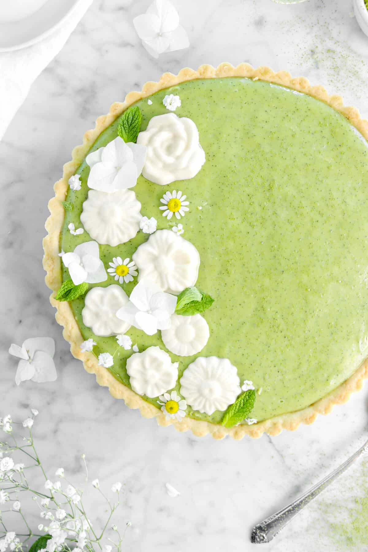 overhead shot of matcha tart on marble counter with white chocolate flowers, fresh flowers, and mint leaves