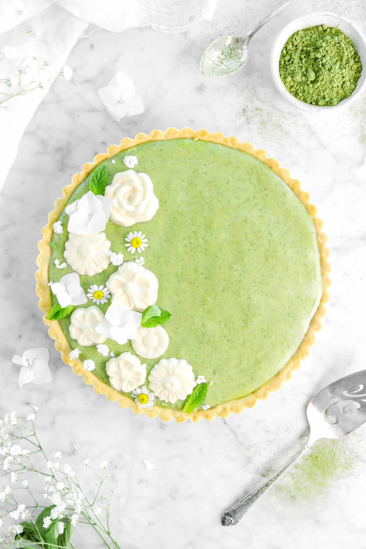 overhead shot of white chocolate matcha tart with flowers, mint leaves, cake knfe, a spoon, bowl of matcha, and a white napkin