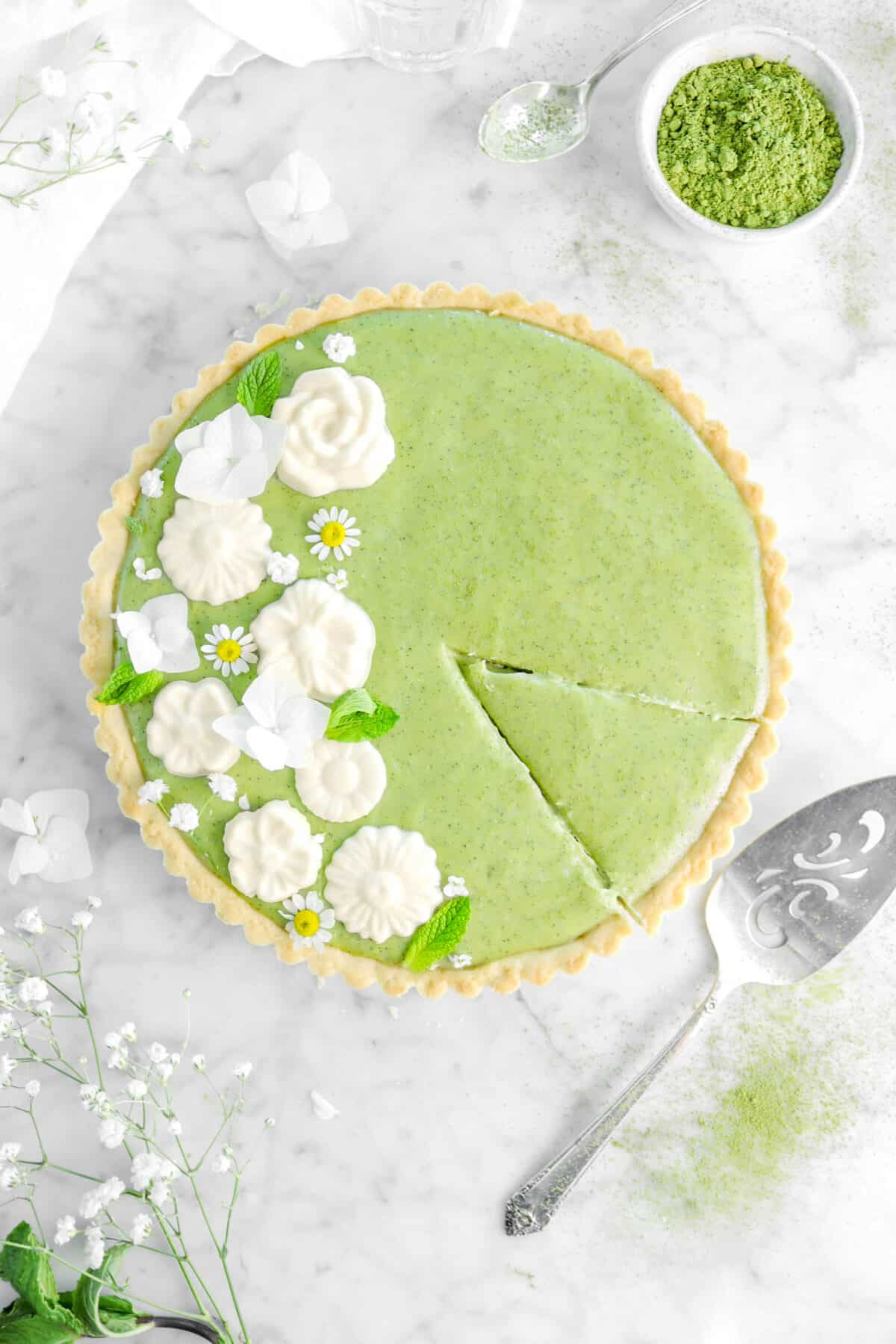 overhead shot of matcha tart with slice cut into it with cake knife beside, matcha powder around, and fresh flowers