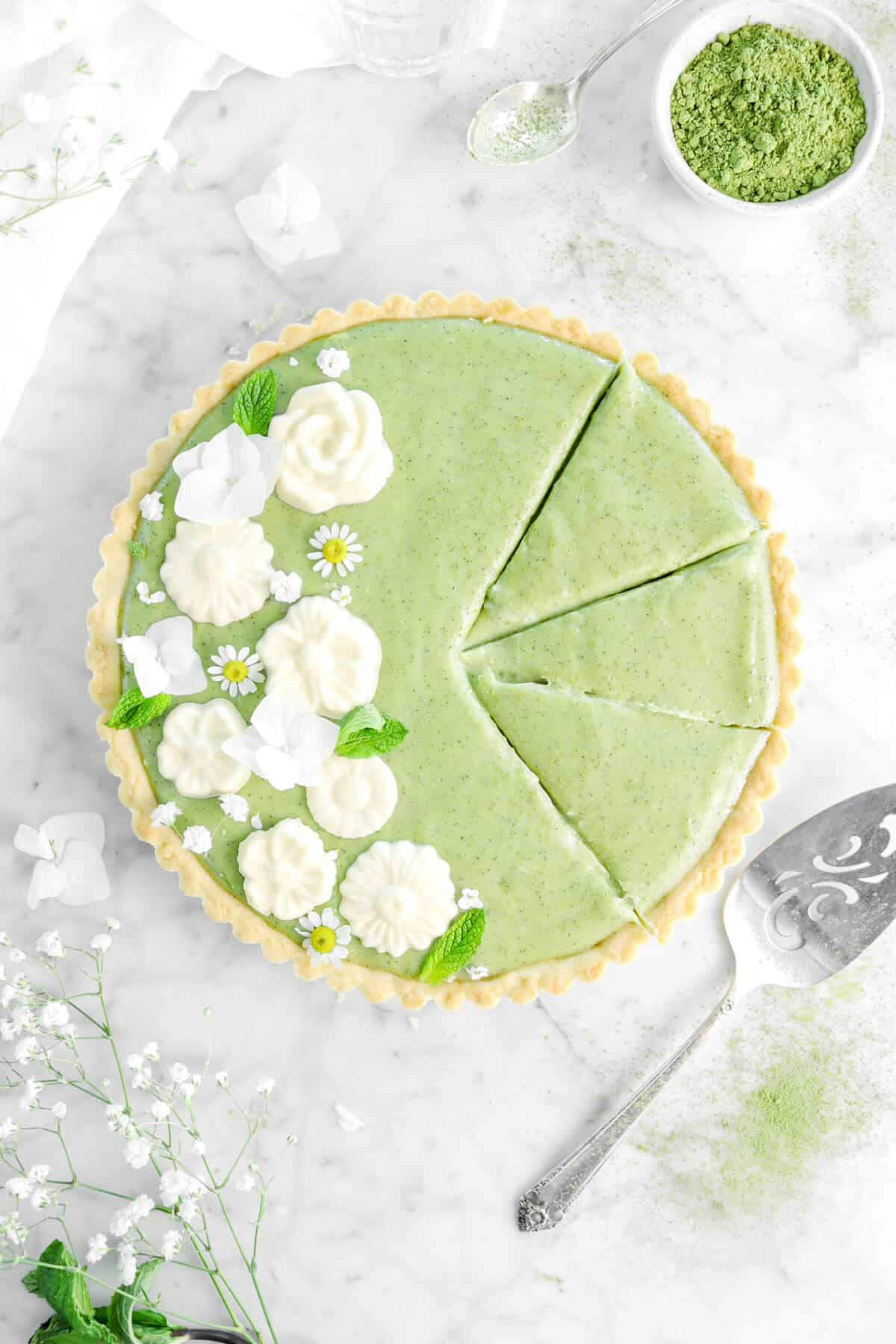 matcha tart with three slices cut into it, fresh flowers, mint leaves, bowl of matcha powder, a spoon, and a cake knife next to the slices