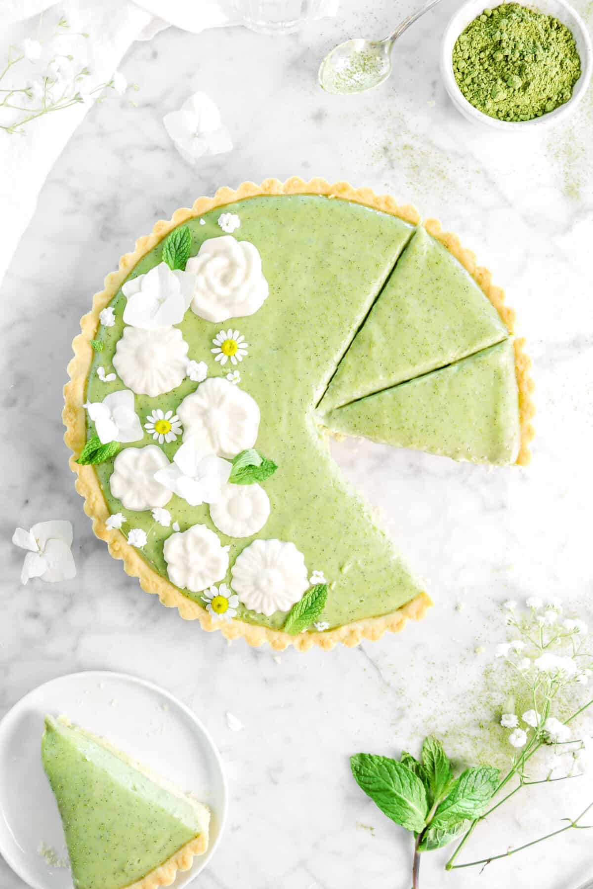 matcha tart with piece missing on a white plate with mint leaves and fresh flowers around