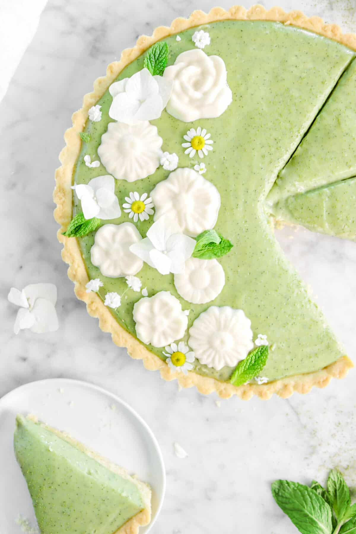 close up of matcha tart on marble counter with a slice on a white palte with white chocolate flowers, fresh flowers, and minut leaves