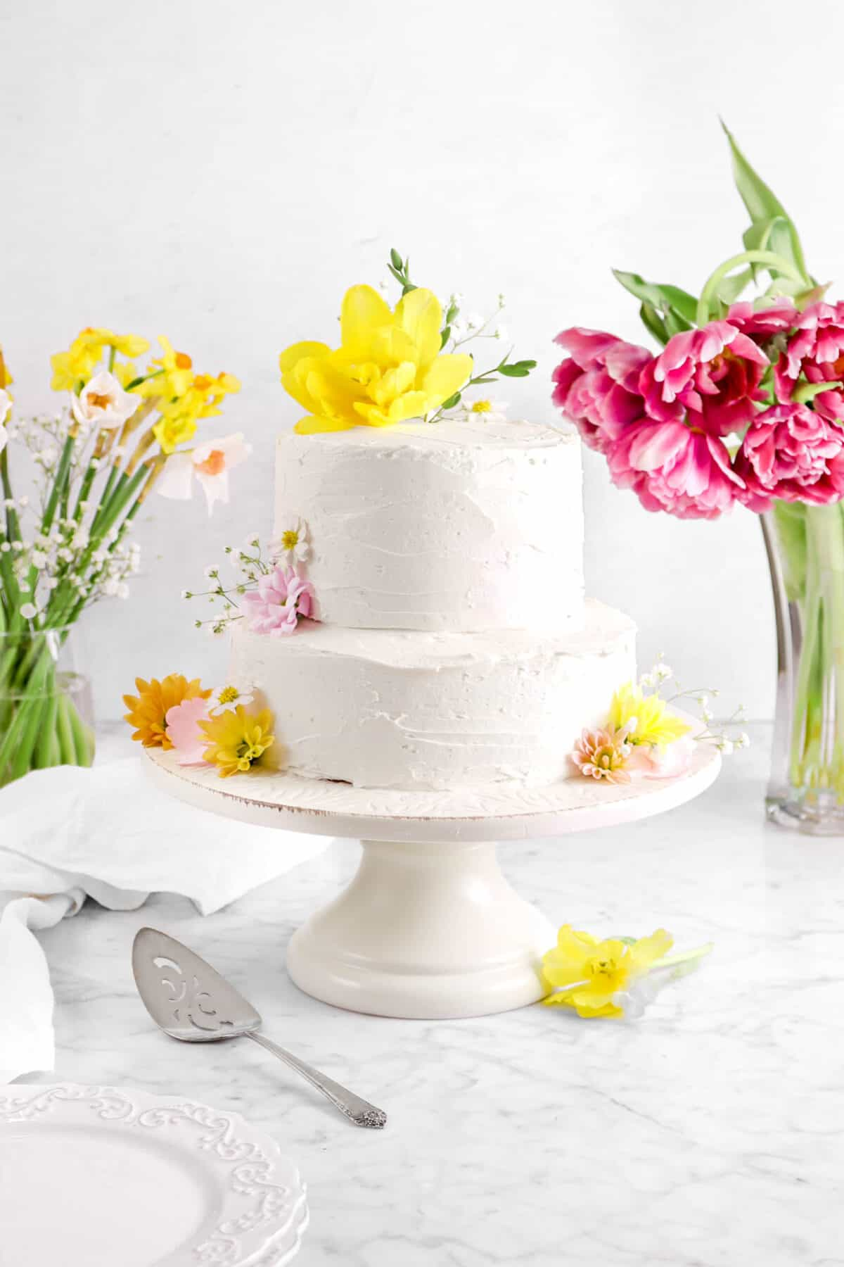 two tier almond layer cake on cake stand with flowers, a cake knife, plates, and napkin