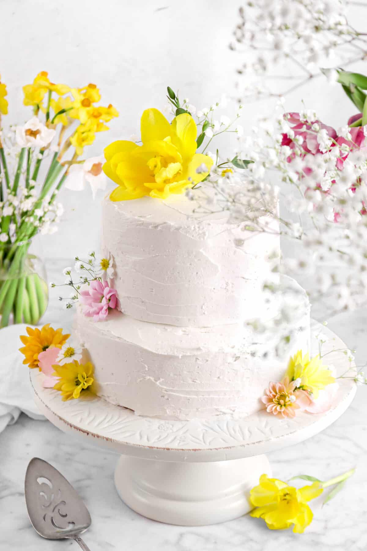 vegan almond cake on cake stand with flowers