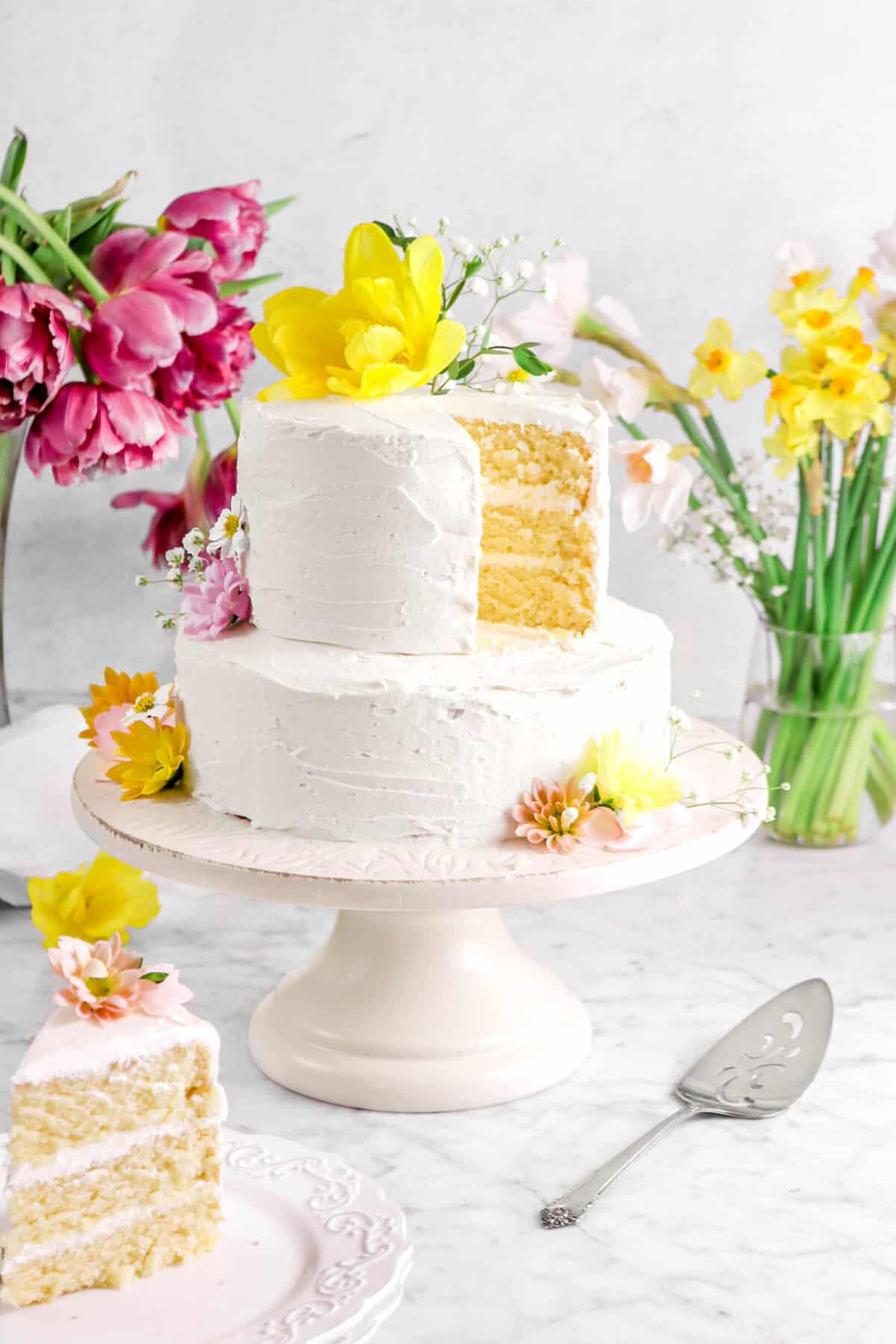 two tier vegan almond cake with flowers, a slice on white plates, and a cake knife