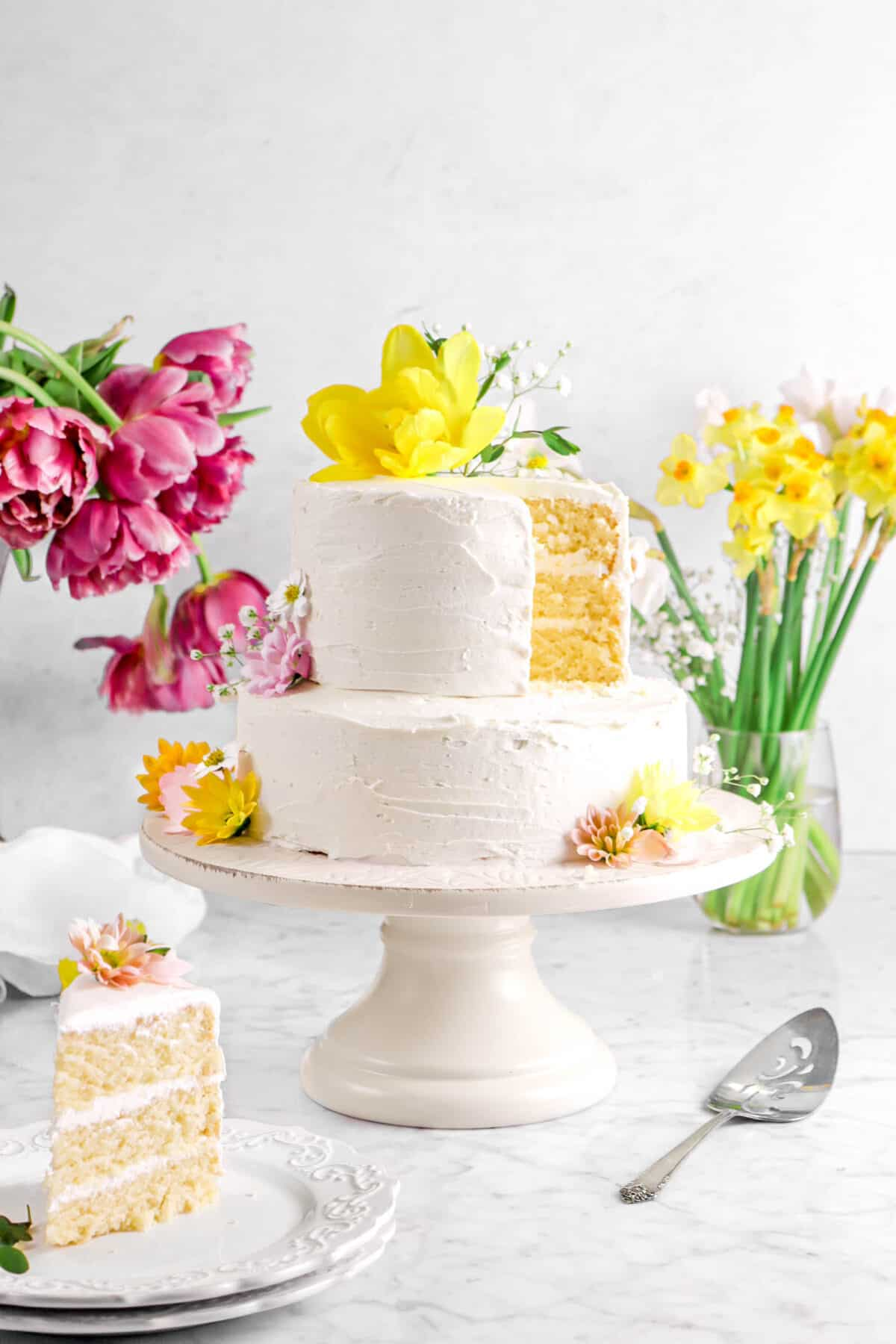 almond cake with a slice on two stacked white plates with flowers behind, a cake knife, and white napkin