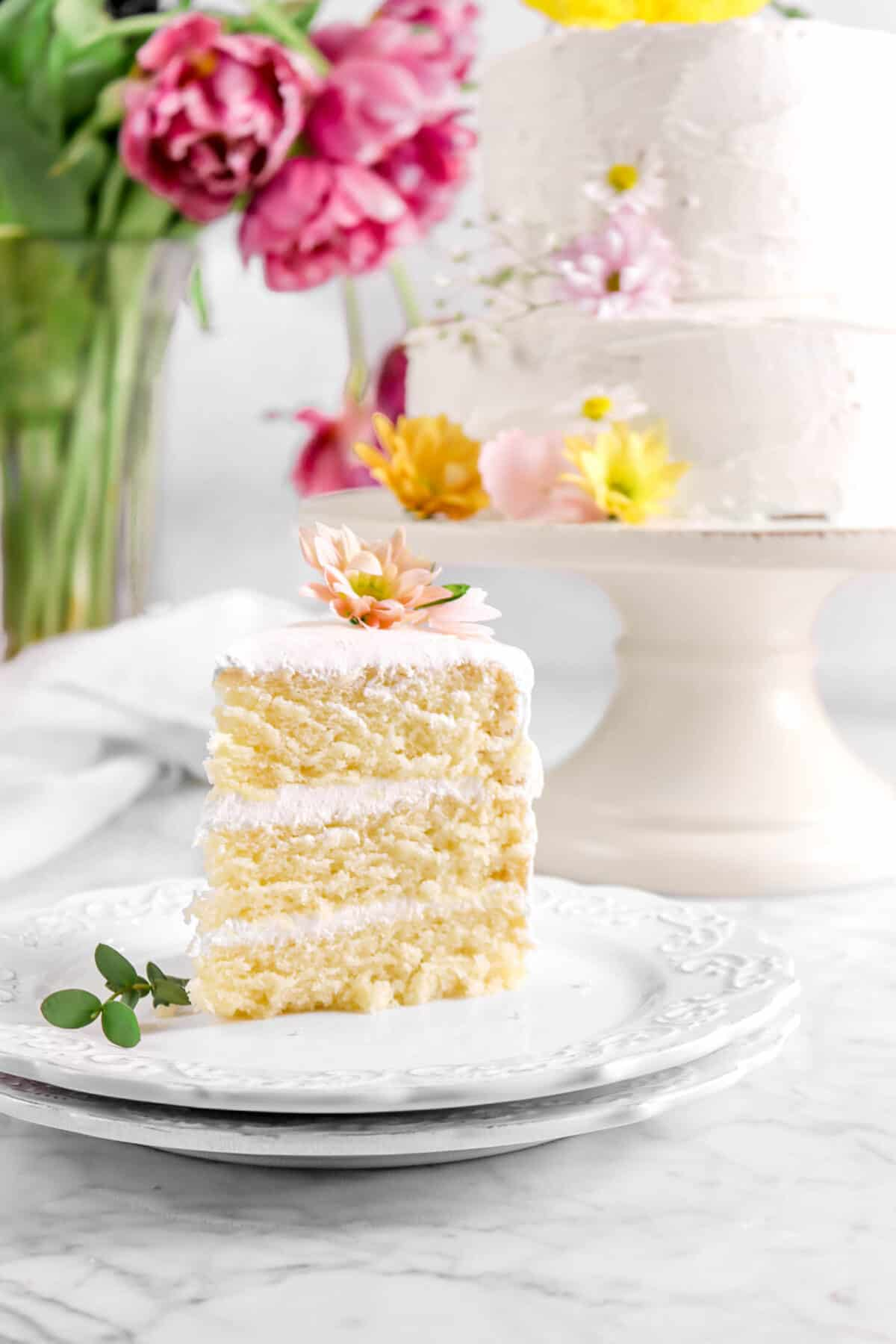 slice of vegan almond cake on white plate with flowers, cake behind, and and pink peonies
