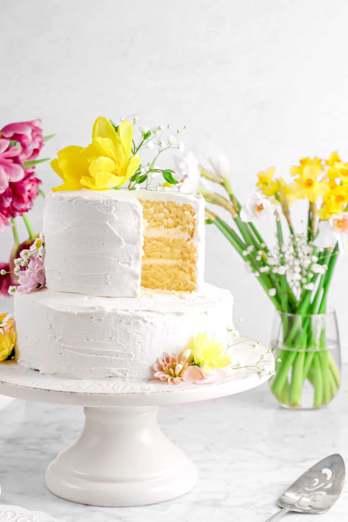 cake on white cake stand with flowers and slice missing from top tier