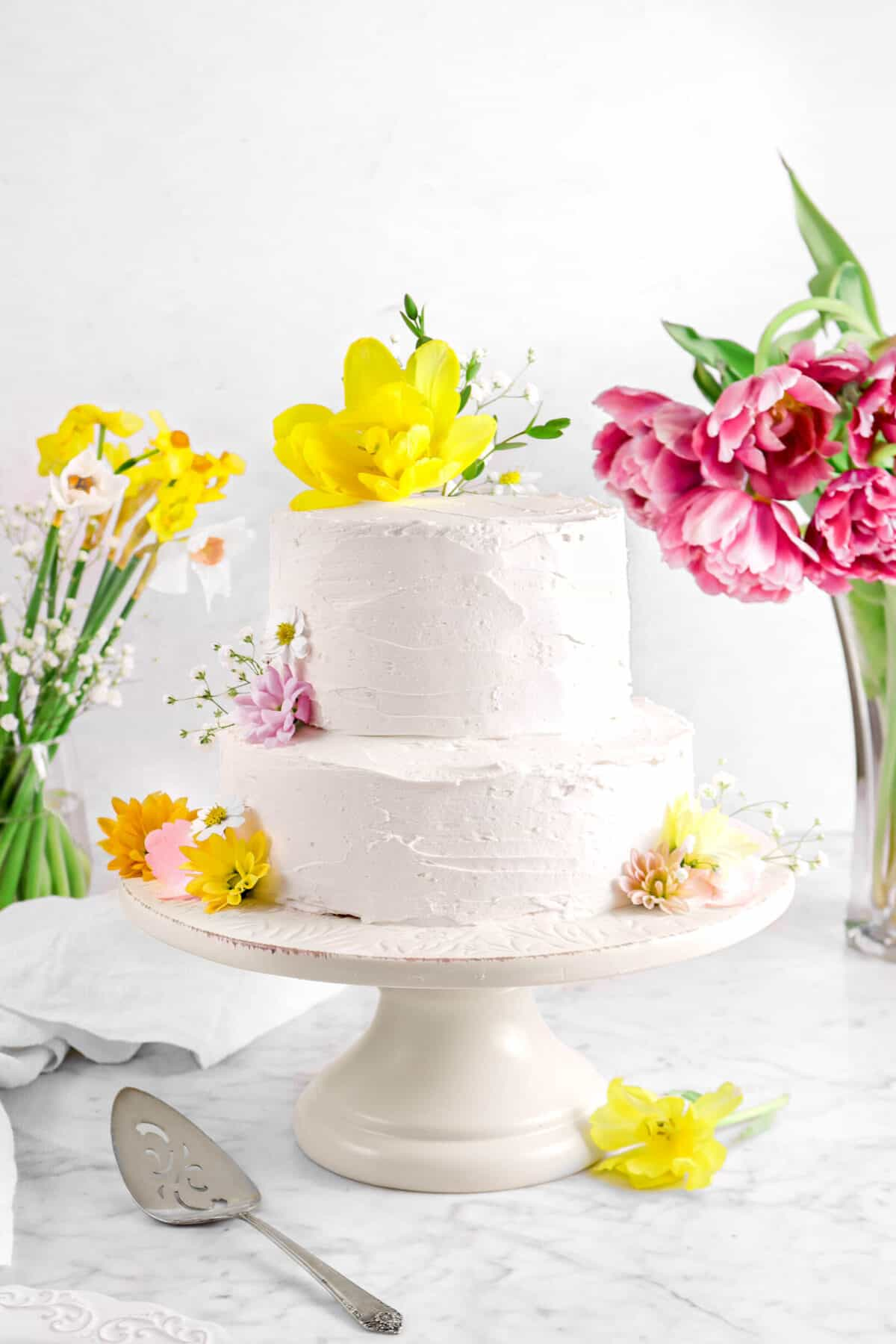 two tier almond layer cake on cake stand with flowers and cake knife