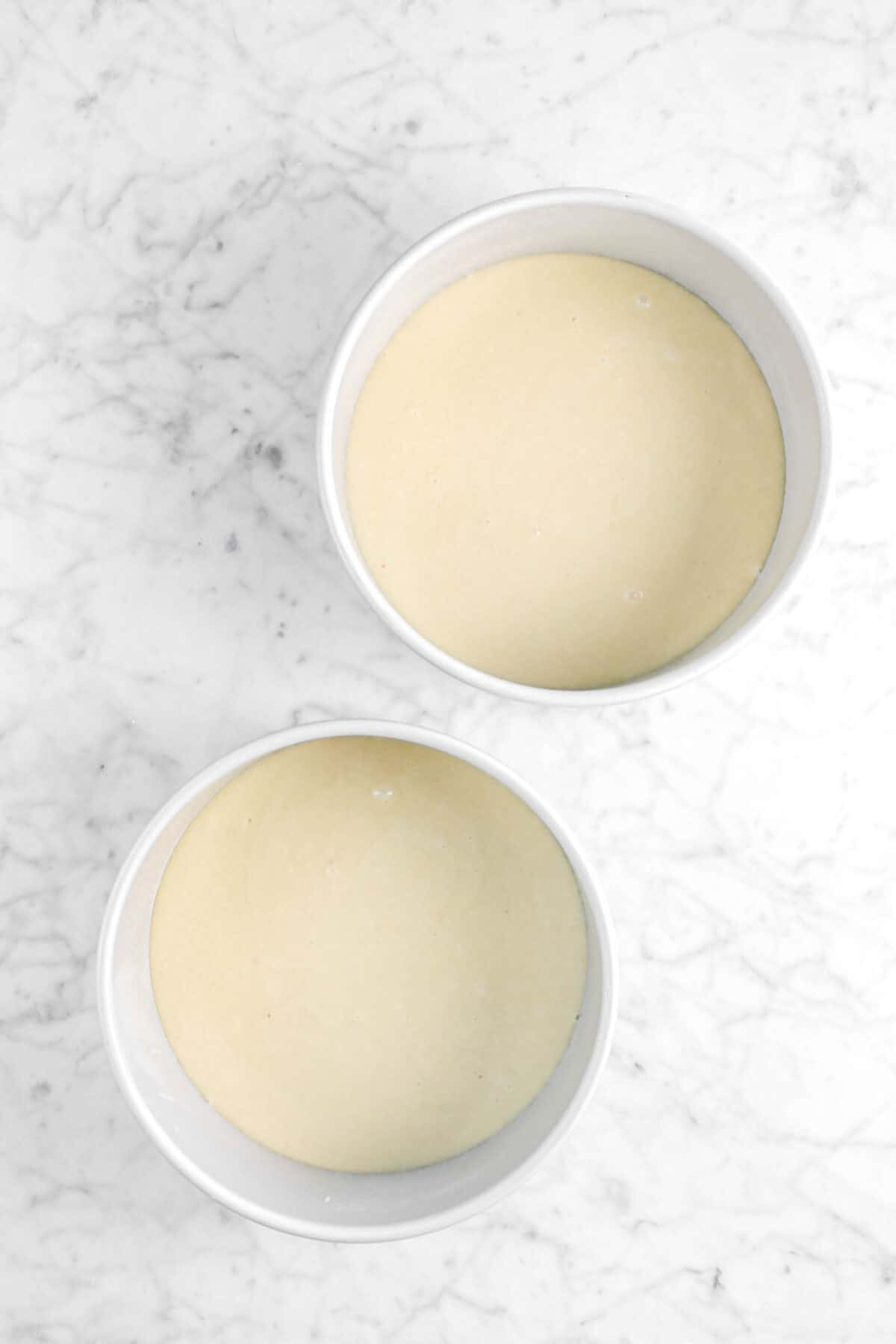 two cake pans with cake batter in marble counter