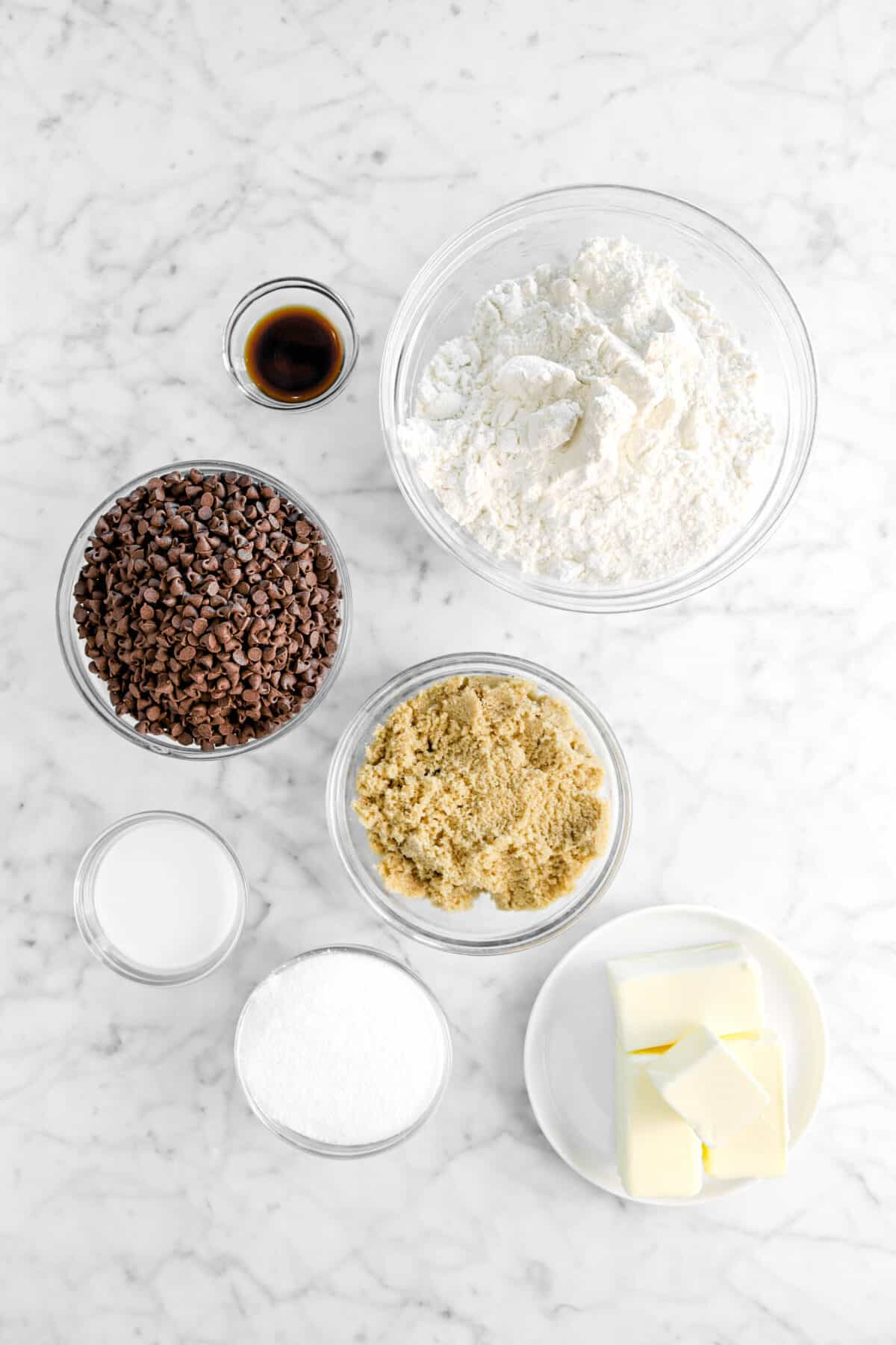 vanilla, flour, chocolate chips, brown sugar, milk, sugar, and butter on marble counter