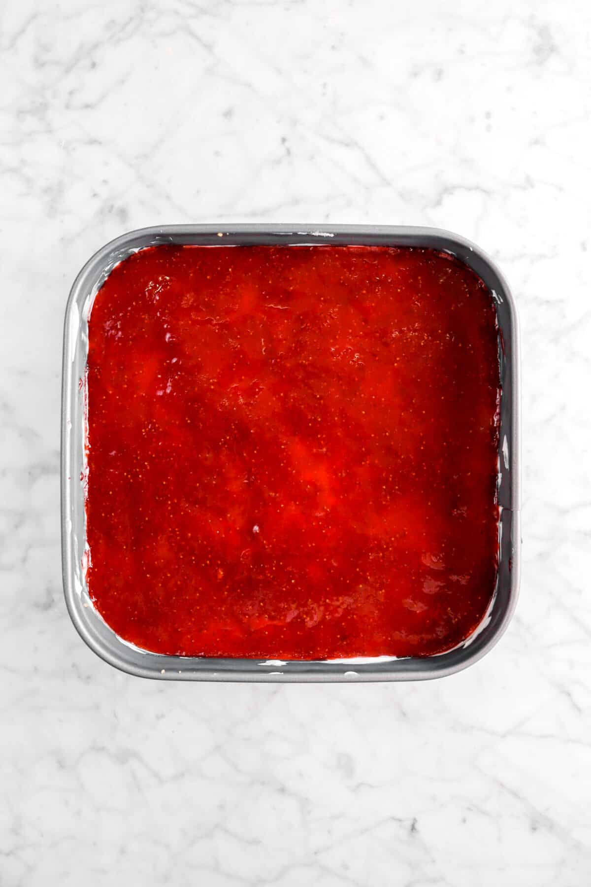 strawberry jam added on top of cheesecake