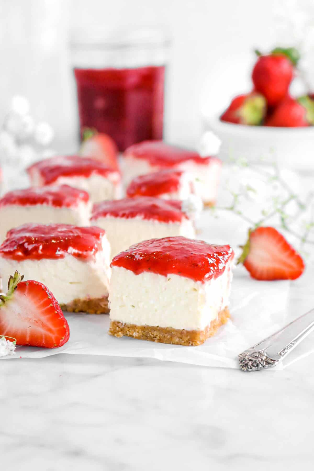 square slices of cheesecake on parchment with strawberries and flowers