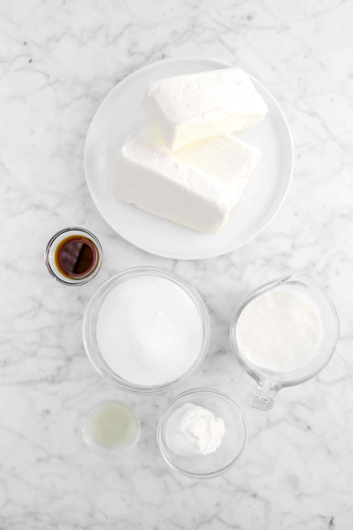 cream cheese, vanilla, sugar, milk, lemon juice, and sour cream in glass bowls on marble counter