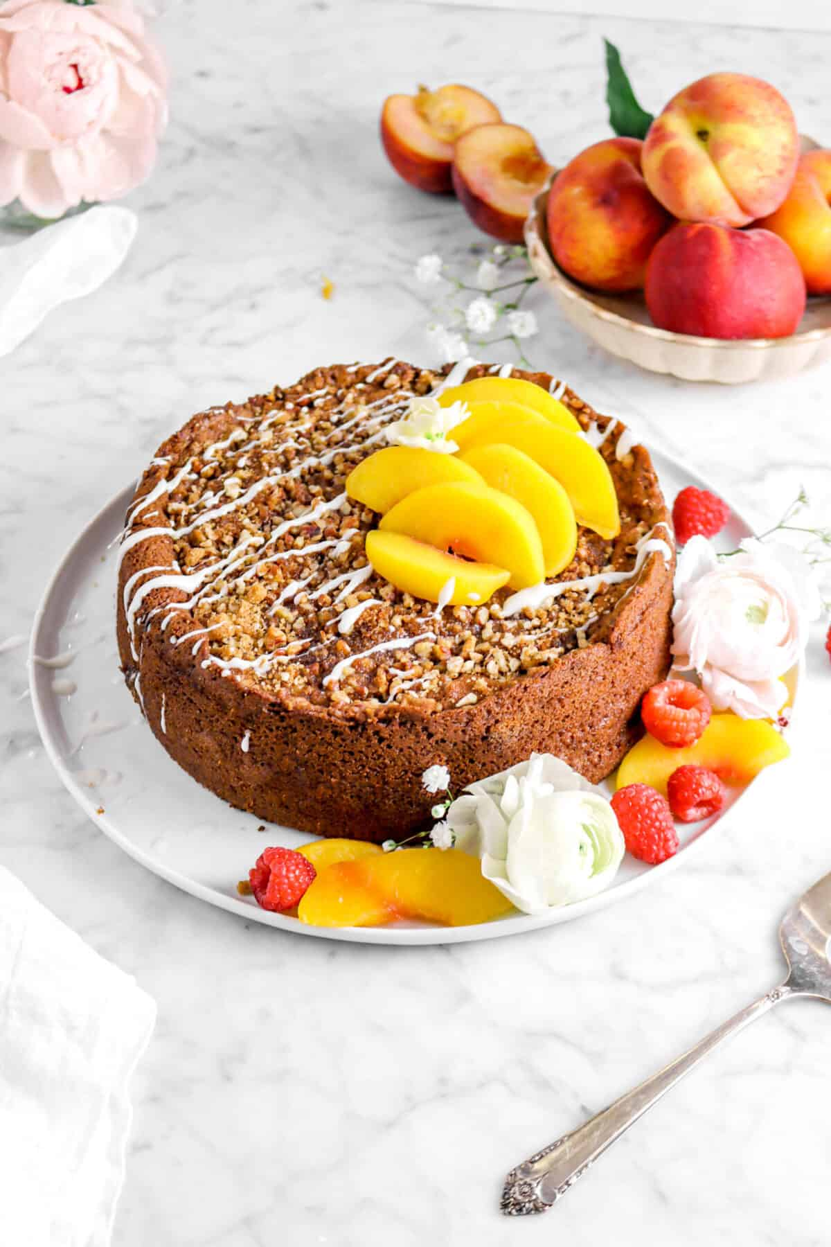 peach cobbler coffee cake on plate with peach slices, flowers, fresh raspberries, and whole peaches behind