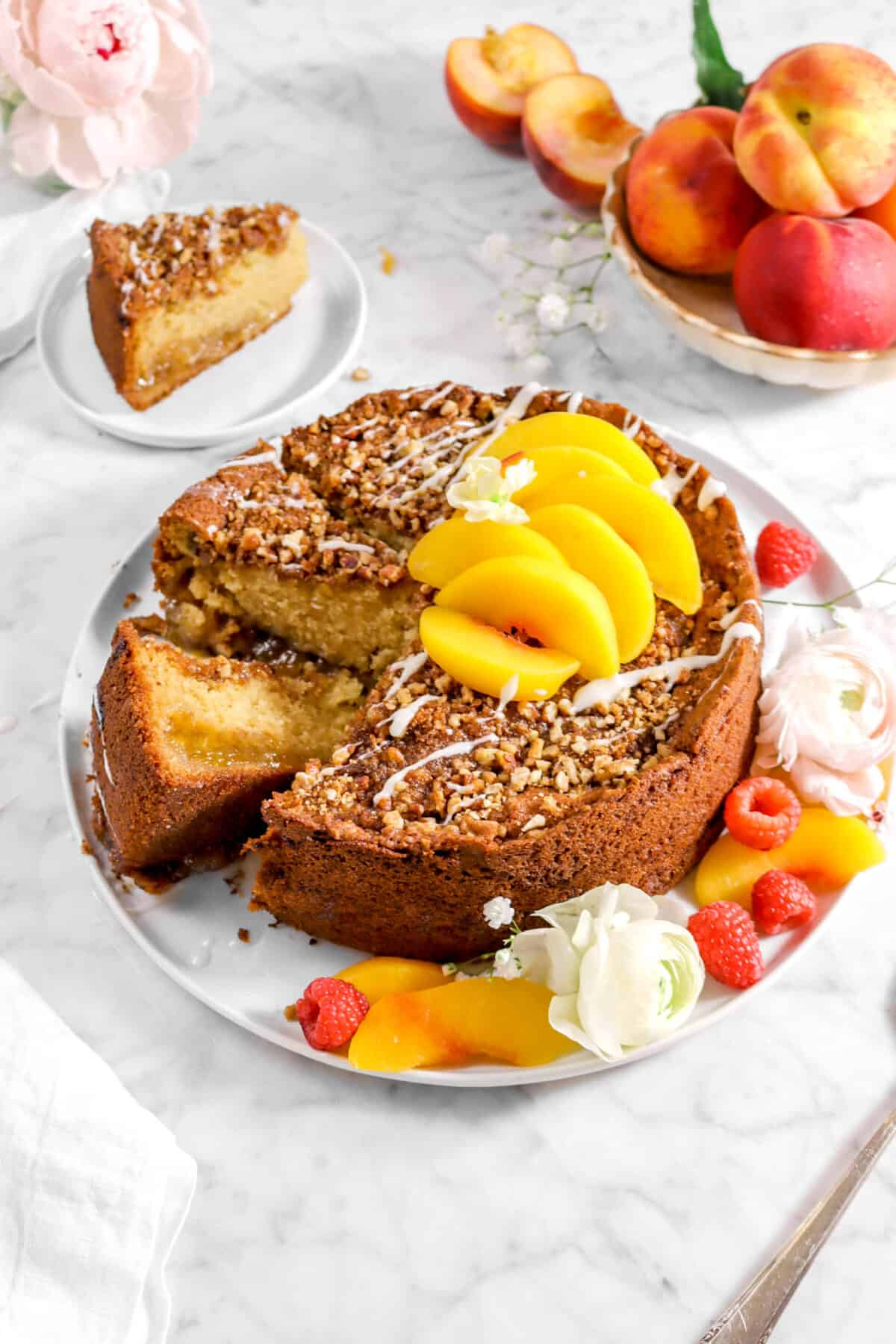 peach coffee cake with two slices laying beside, fresh peach slices on top, flowers, and a slice of cake behind