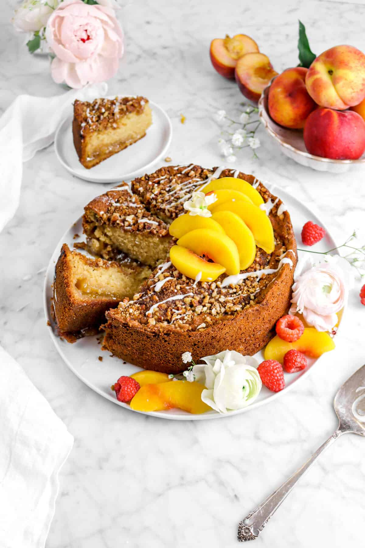 peach coffee cake on white plate with two slices laying beside cake, one behind on white plate, with fresh berries, peach slices, and flowers