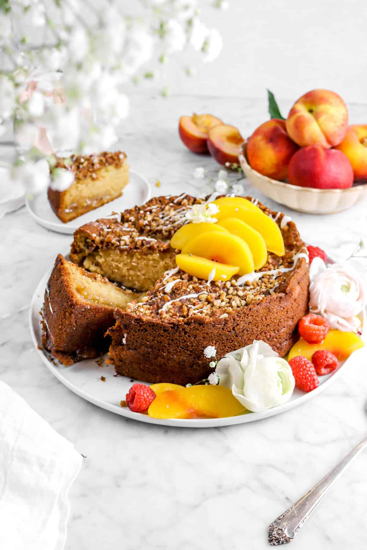 peach coffee cake on white plate with peaches, raspberries, flowers, whole peaches behind, and baby's breath flowers in front