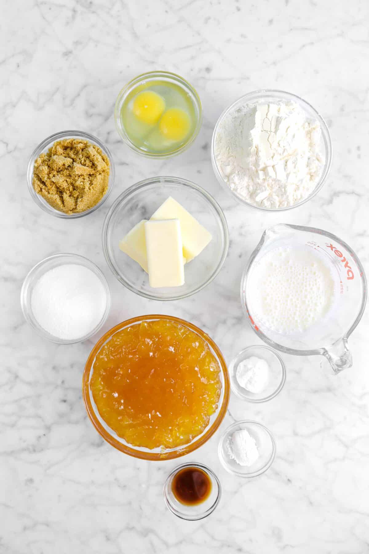 eggs, flour, brown sugar, butter, buttermilk, sugar, peach preserves, baking soda, baking powder, and vanilla in glass bowls