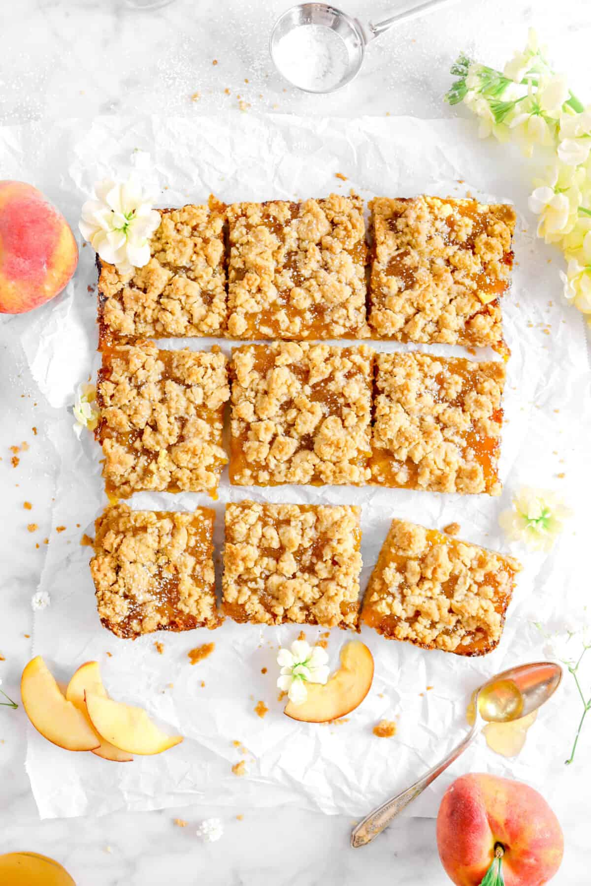 overhead shot of nine peach crumble bars with flowers, peaches, and honey