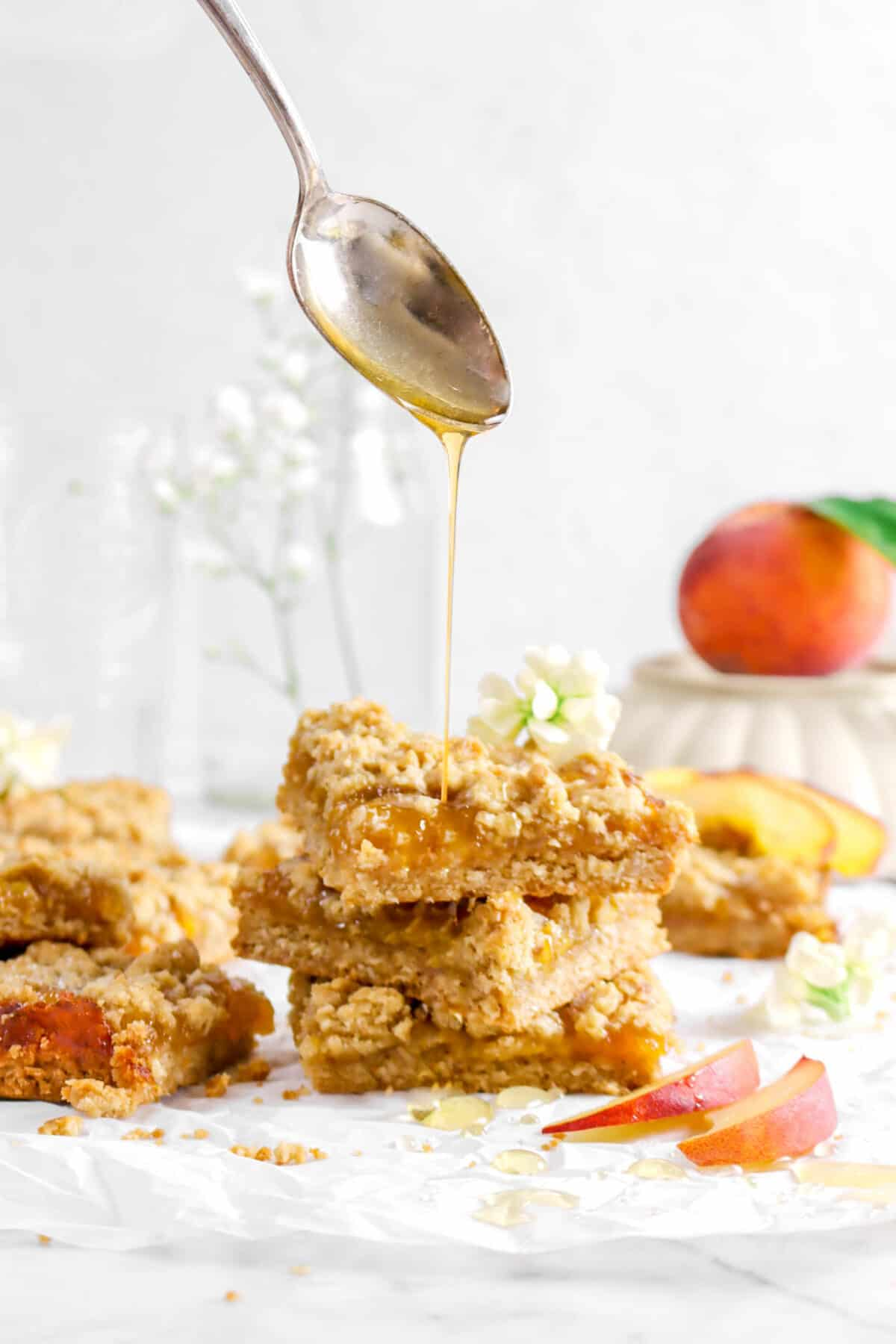 honey being poured onto stacked crumble bars