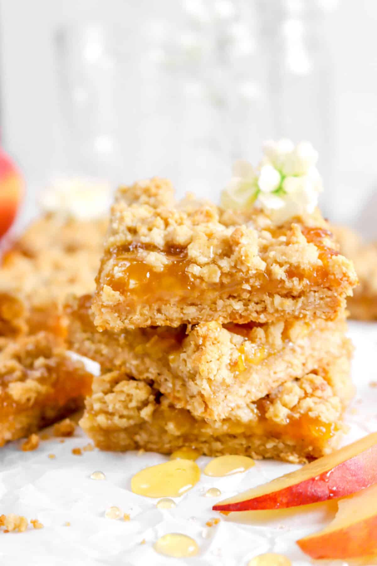 close up of stacked peach crumble bars