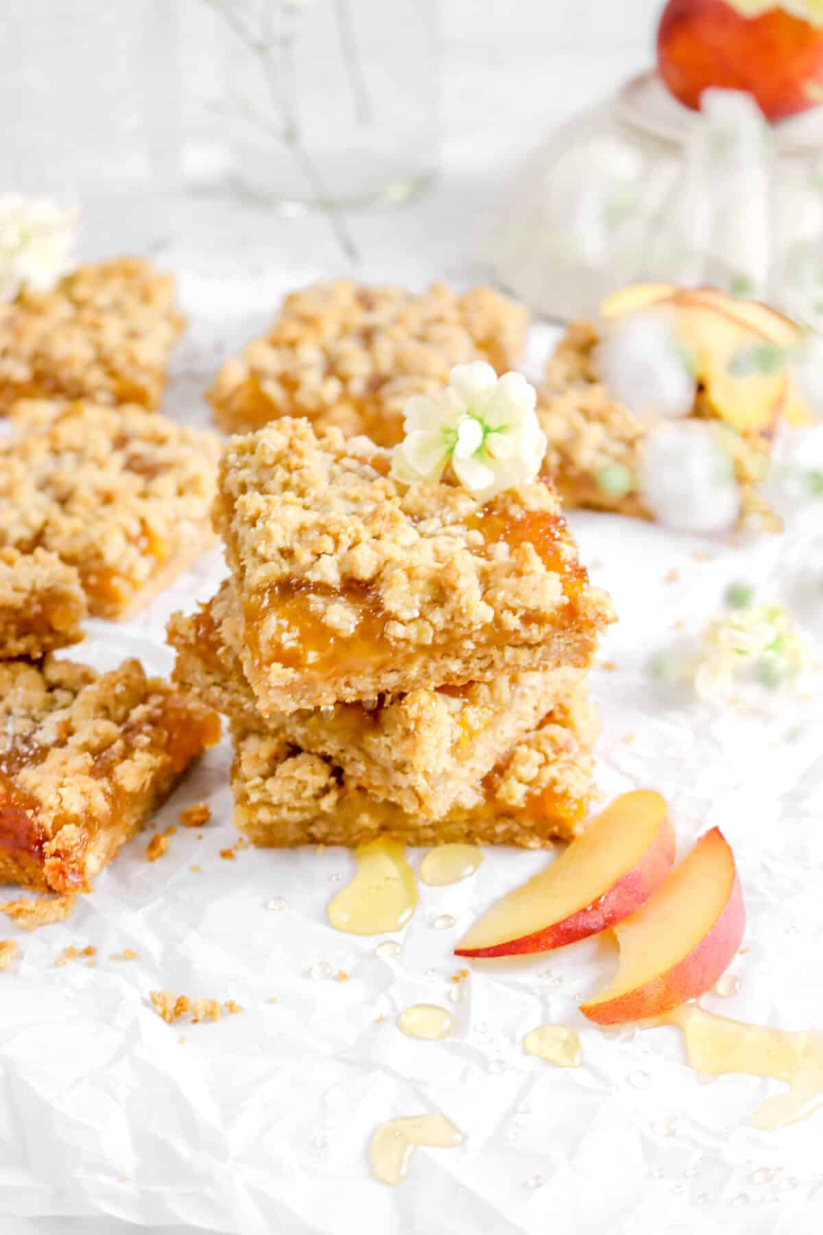three stacked peach crumble bars with flowers and honey drizzle