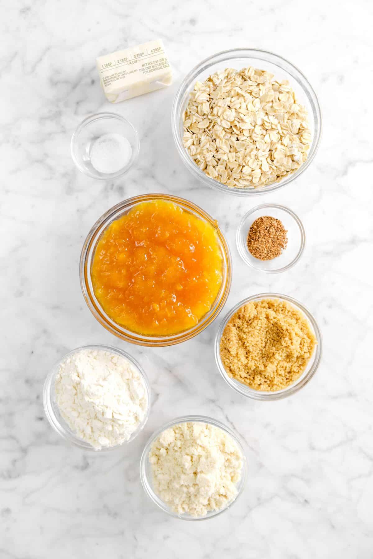 butter, oats, salt, peach jam, nutmeg, brown sugar, flour, almond flour in glass bowls
