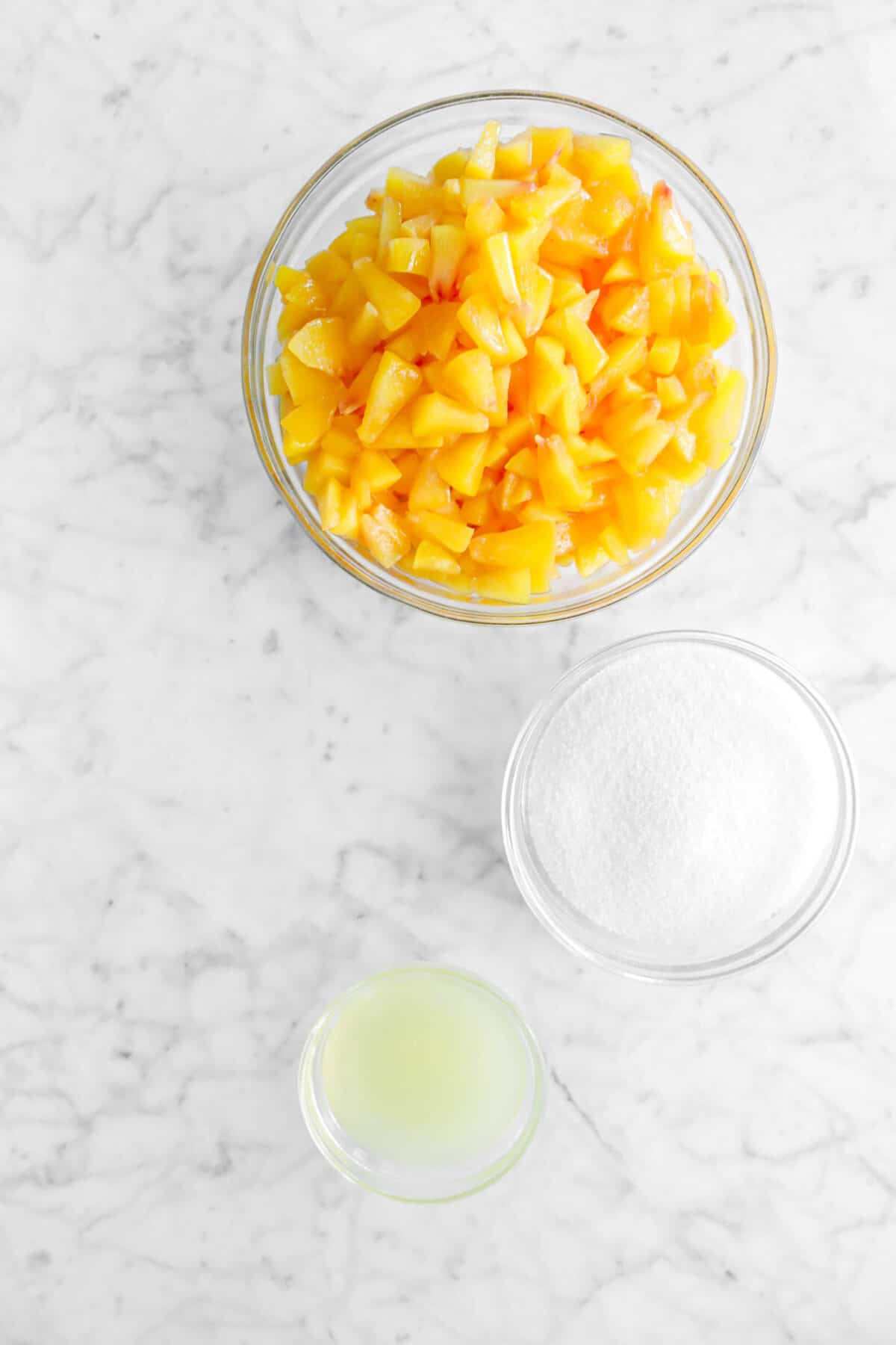 chopped peaches, sugar, and lemon juice in glass bowls