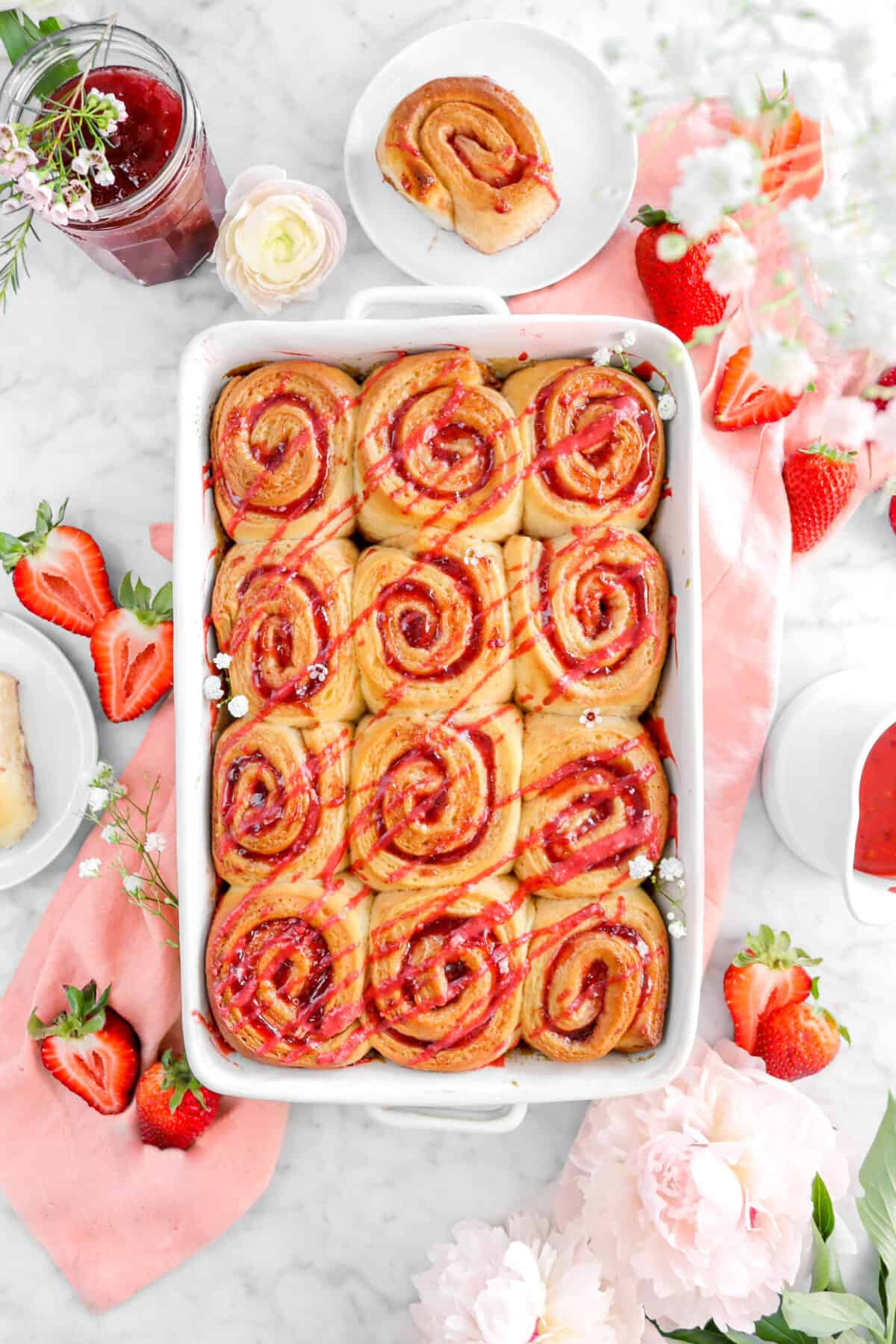 strawberry rolls with strawberry icing on pink napkin with flowers, strawberries, and more rolls around