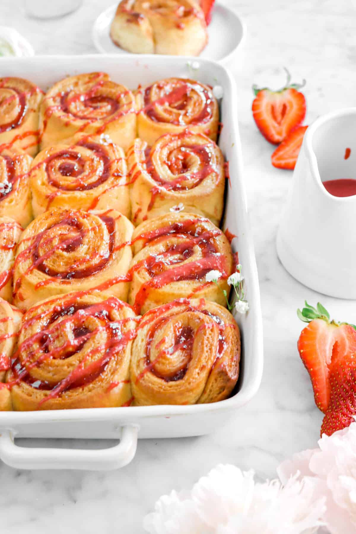 close up of strawberry rolls in white pan