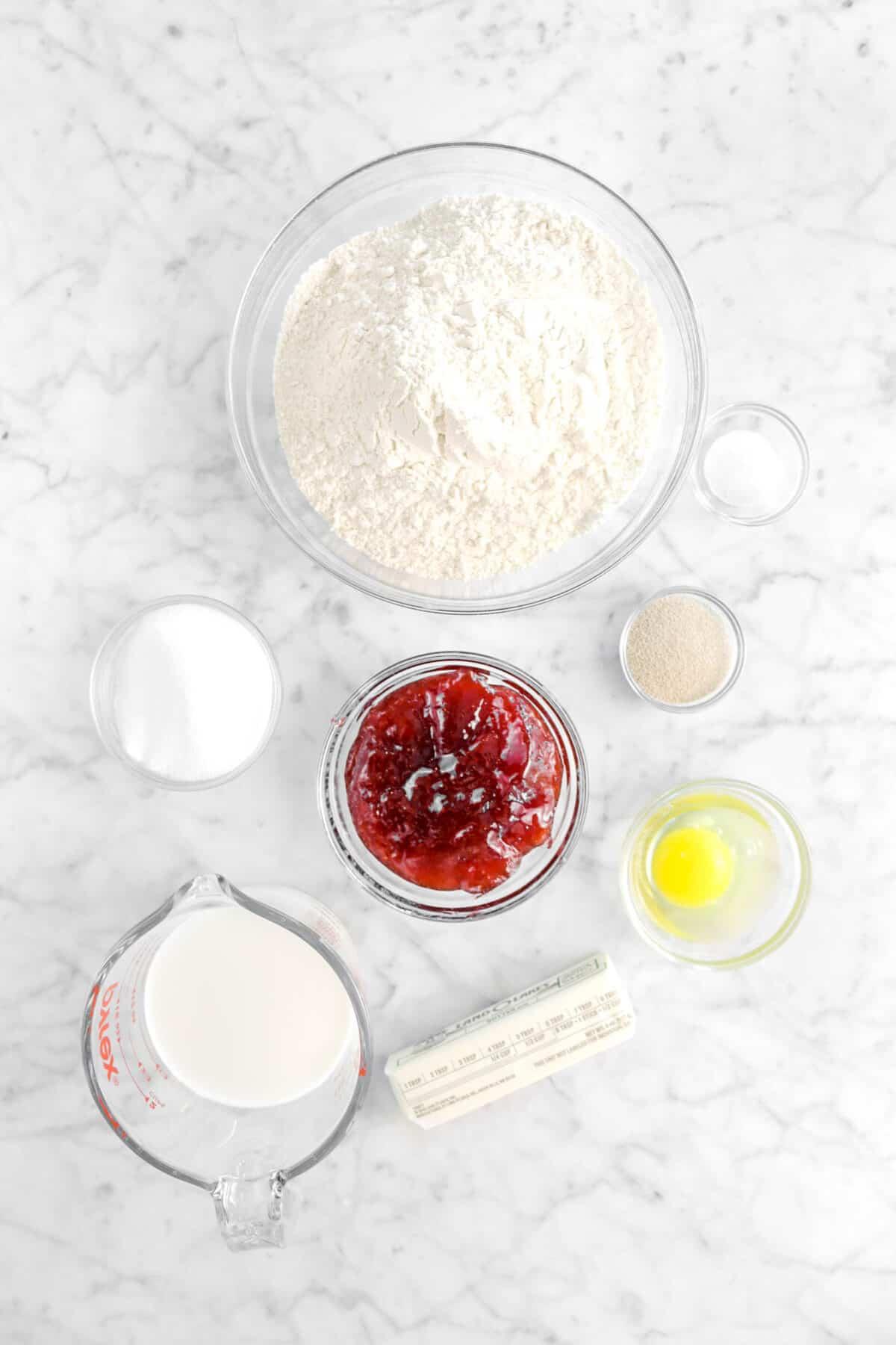 flour, salt, yeast, sugar, strawberry jam, egg, flour, and milk on marble counter