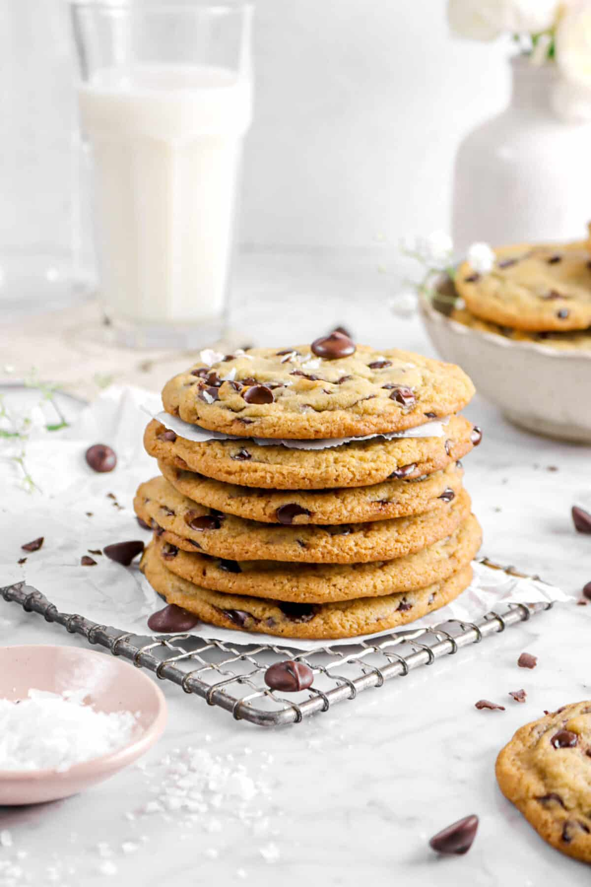 close up of stacked chocolate chip cookies with pink bowl of salt beside and glass of milk behind