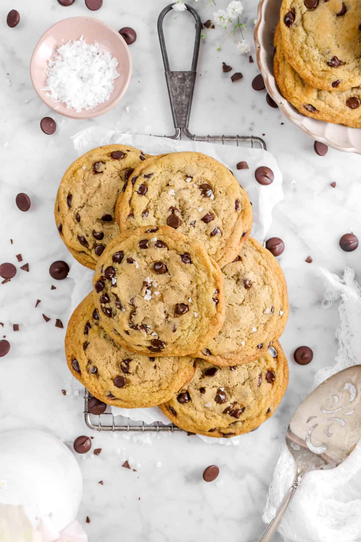 overhead shot of six cookies on tray with chocolate chips, a bowl of salt, and a cake knife
