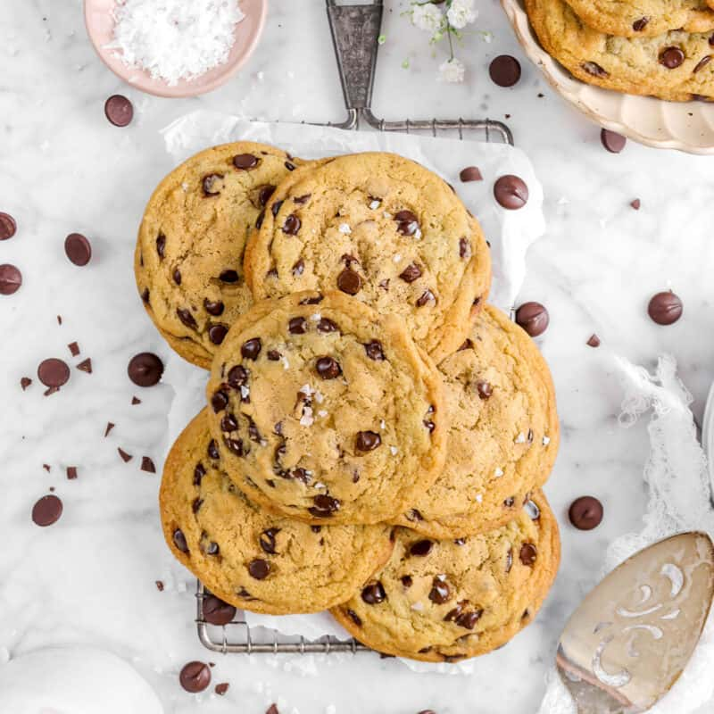 six chocolate chip cookies on serving tray with chocolate chips, a bowl of cookies, a bowl of salt, flowers, and a cake knife